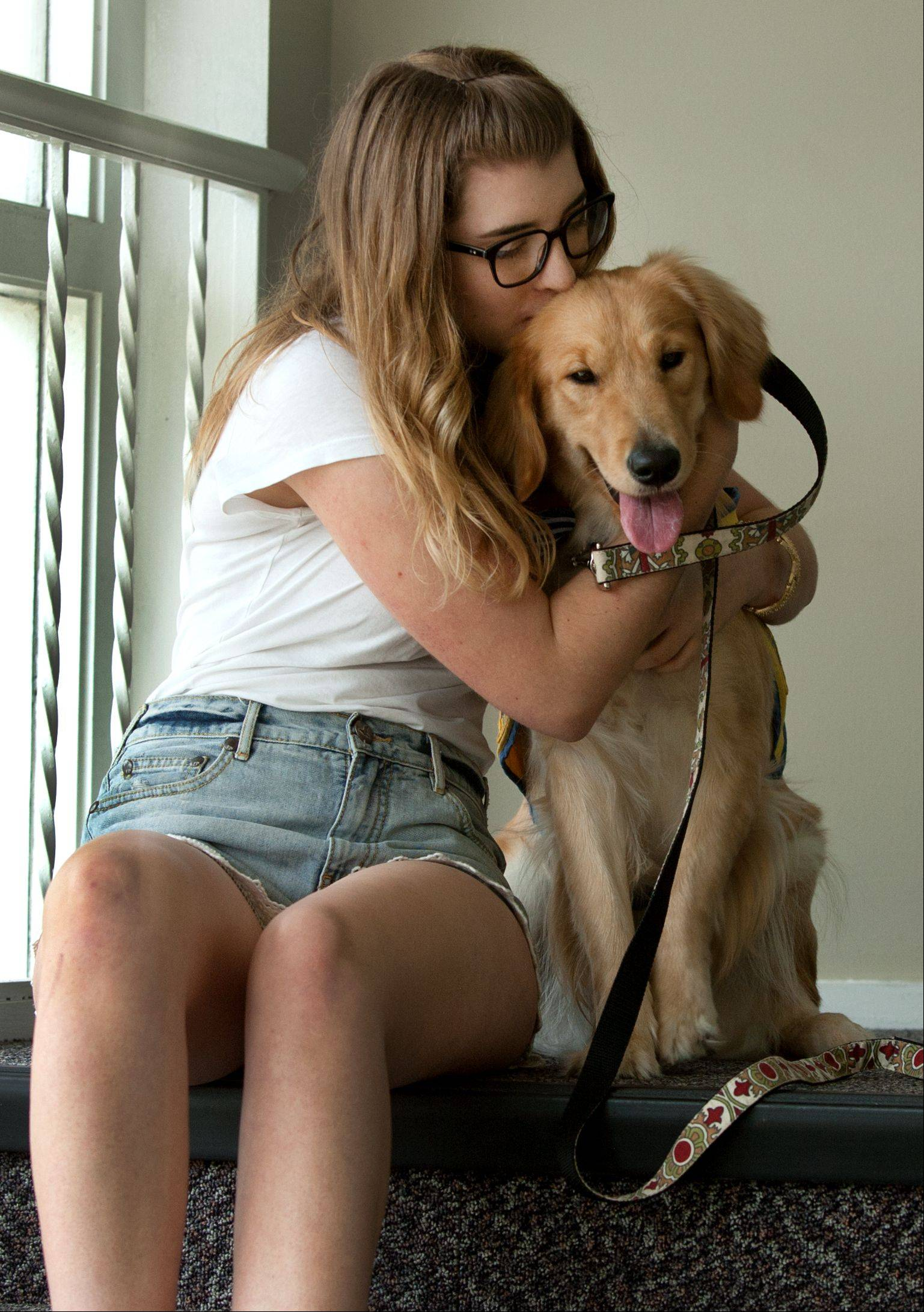 Morgan Riley cuddles with Friday, a 1-year-old golden retriever she is raising to be a service dog for people with disabilities. Service dogs must be hardworking, docile and lovable, she says.