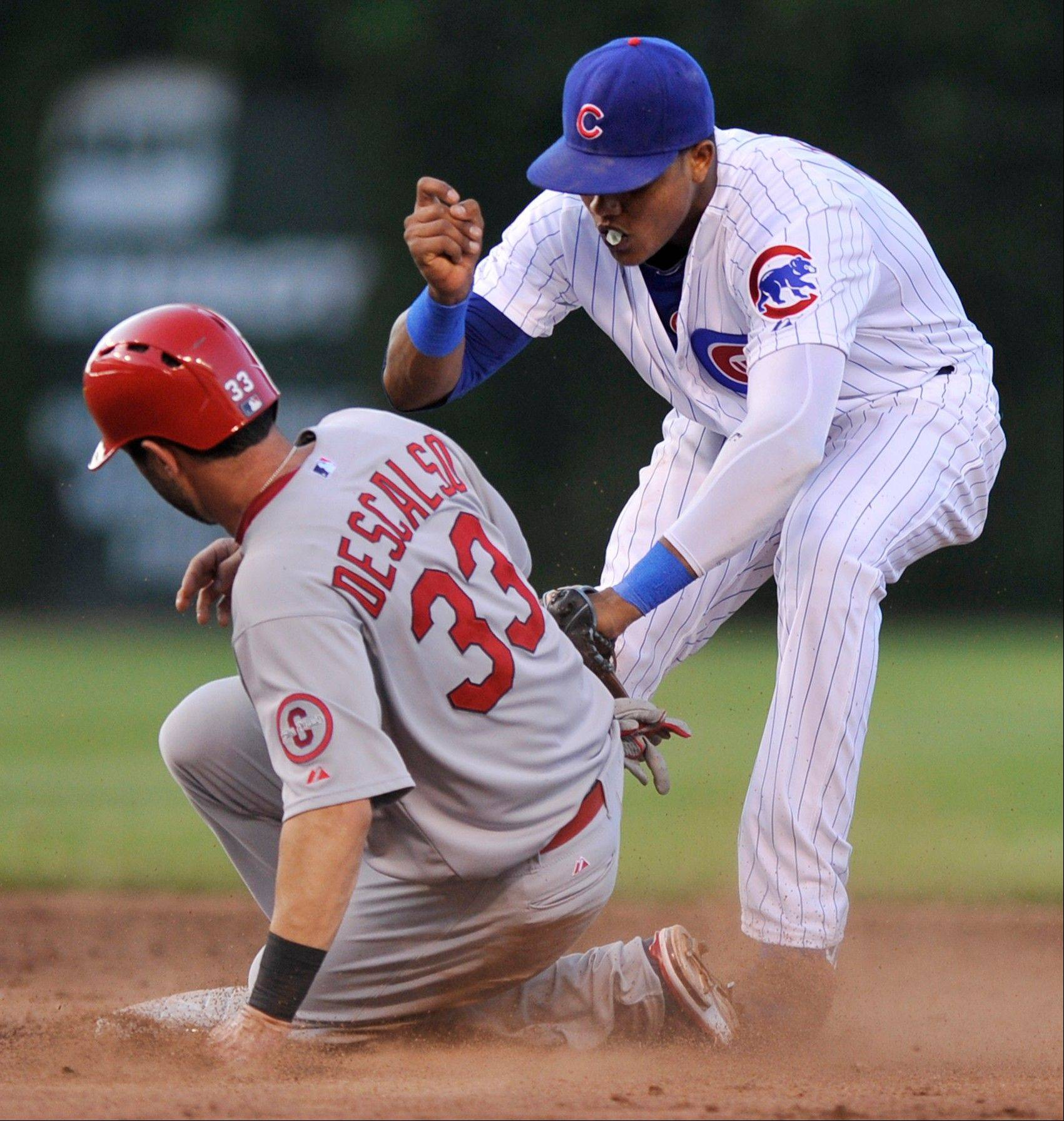 Chicago Cubs shortstop Starlin Castro, right, tags out St. Louis Cardinals' Daniel Descalso (33) who was trying to steal second base during the third inning of a baseball game in Chicago, Saturday, July 13, 2013.