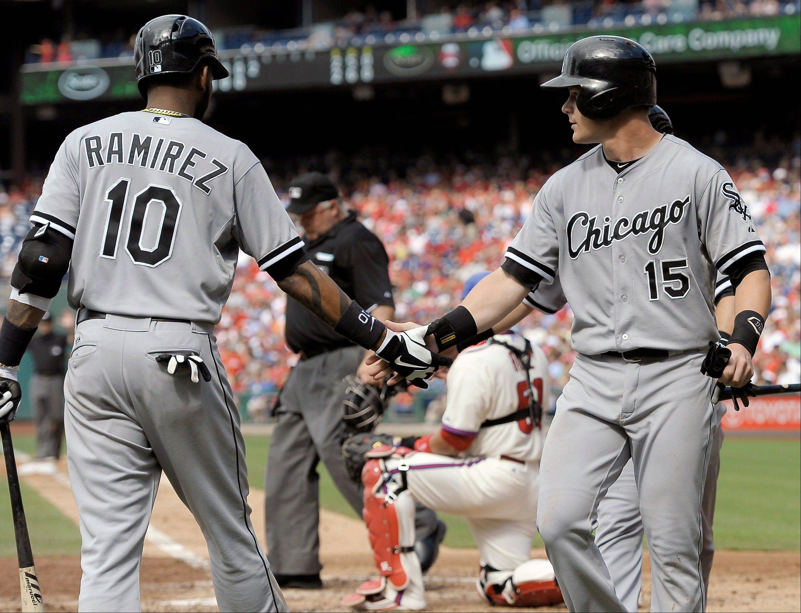 Chicago White Sox's Gordon Beckham (15) is greeted by Alexei Ramirez after scoring on an Alejandro De Aza double in the fifth inning during game one of a baseball doubleheader against the Philadelphia Phillies on Saturday, July 13, 2013, in Philadelphia.