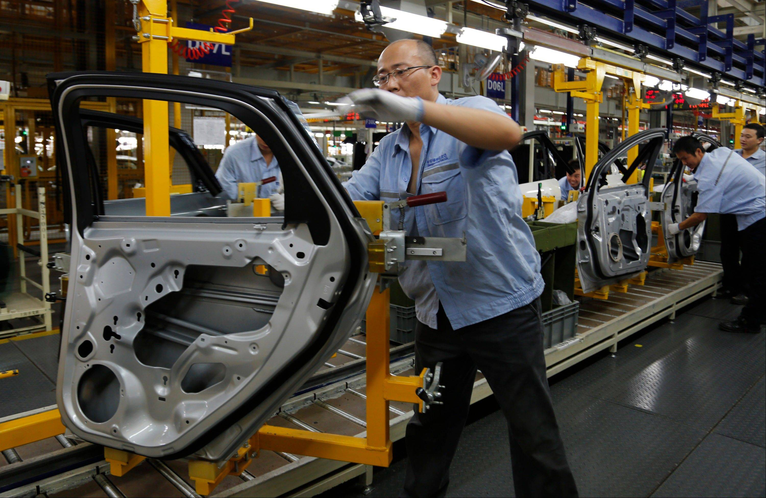 In this Monday, Aug. 27, 2012 photo provided by Ford Motor Co., workers assemble a car at a new Ford/CFMA Chongqing Plant after its launching ceremony in Chongqing, China. Ford aims to increase its share of the market as more Chinese consumers buy vehicles.