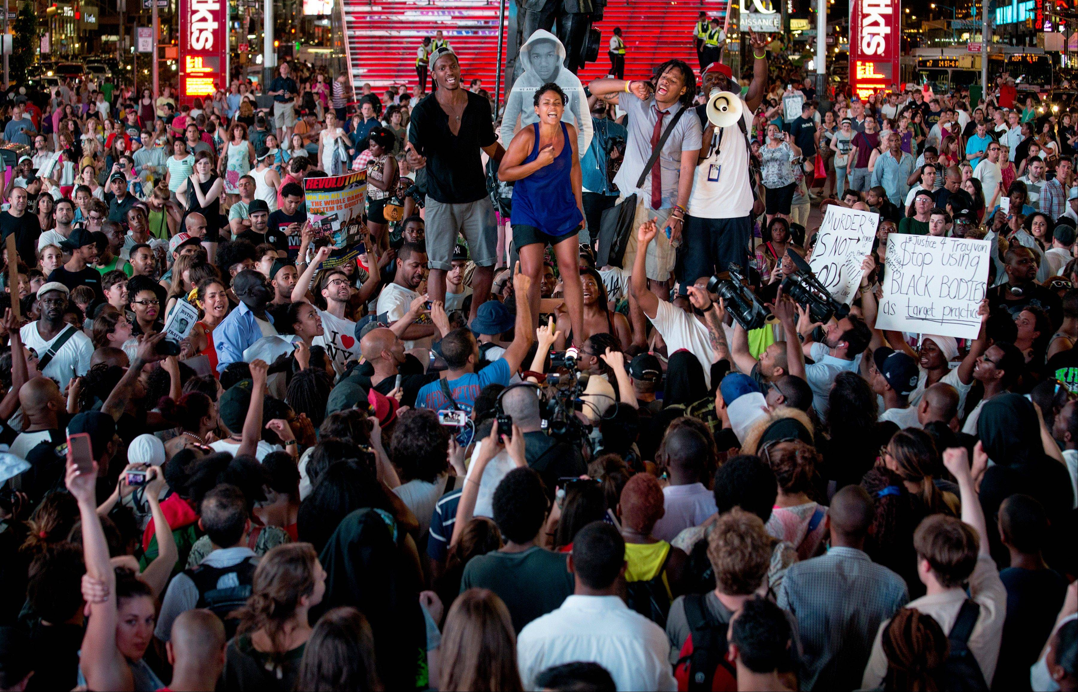Throngs of marches gather on Times Square as they listen to a speaker Sunday in New York for a protest against the acquittal of volunteer neighborhood watch member George Zimmerman in the 2012 killing of 17-year-old Trayvon Martin.