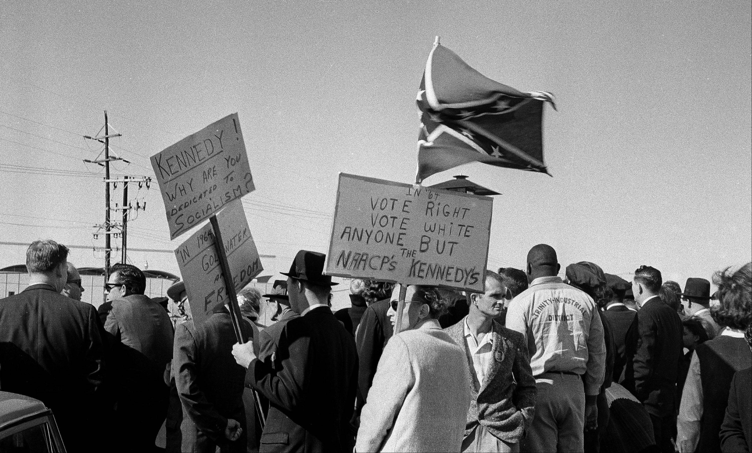 On Nov. 22, 1963, right-wing protesters carrying a Confederate flag and anti-Kennedy placards await the arrival of President John F. Kennedy at Love Field in Dallas. The 50th anniversary of Kennedy's assassination throws a new spotlight on the deep hostility toward Kennedy that some Dallasites voiced before the assassination.