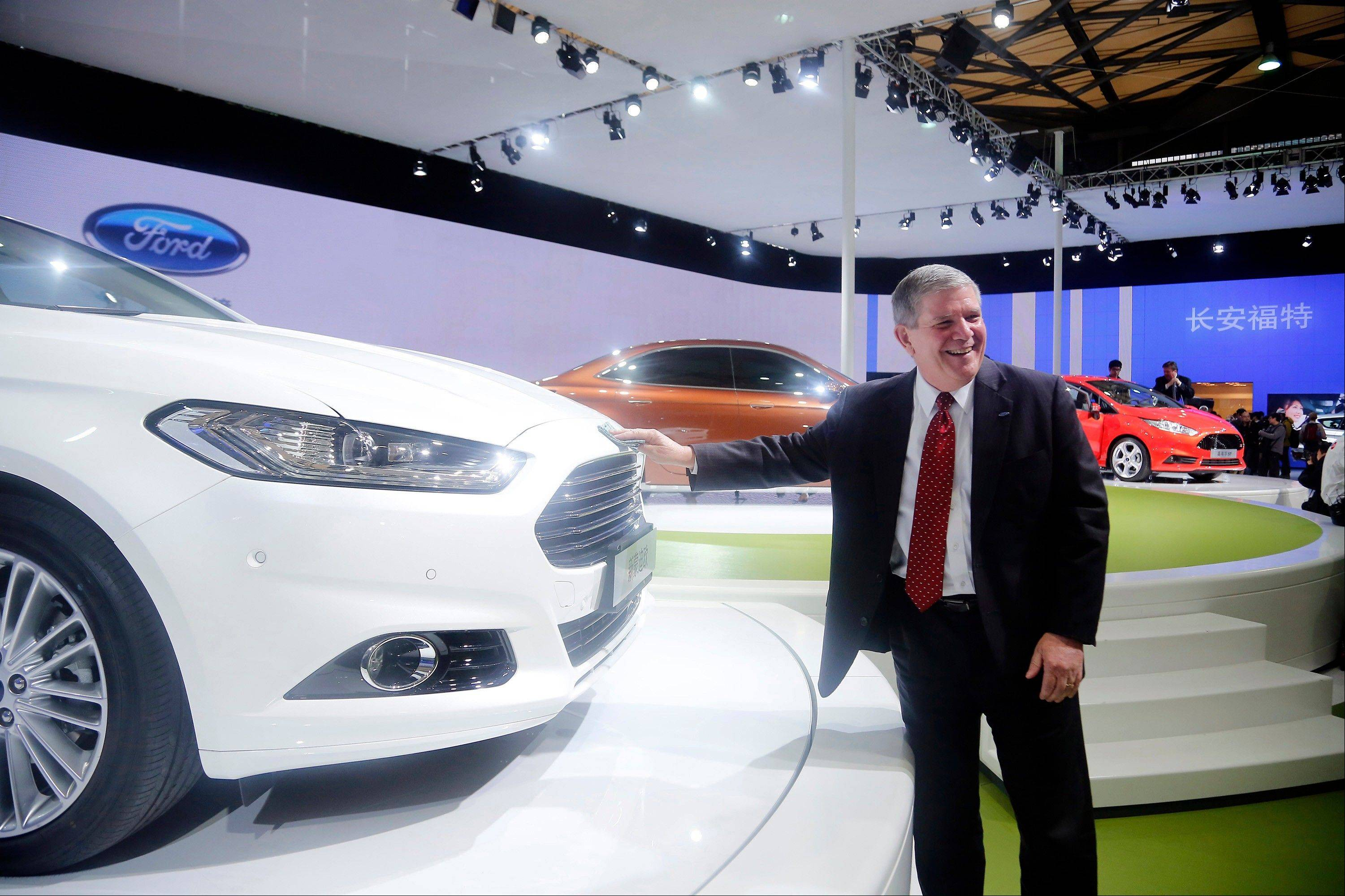 In this photo taken April 20, 2013, David Schoch, Ford Motor Company group vice president and president, Asia Pacific, poses for photos by Ford's new Mondeo car at the Shanghai Auto Show in Shanghai, China. Late to the Chinese auto market, Ford aims to catch up with new cars, new plants, and a new attitude.