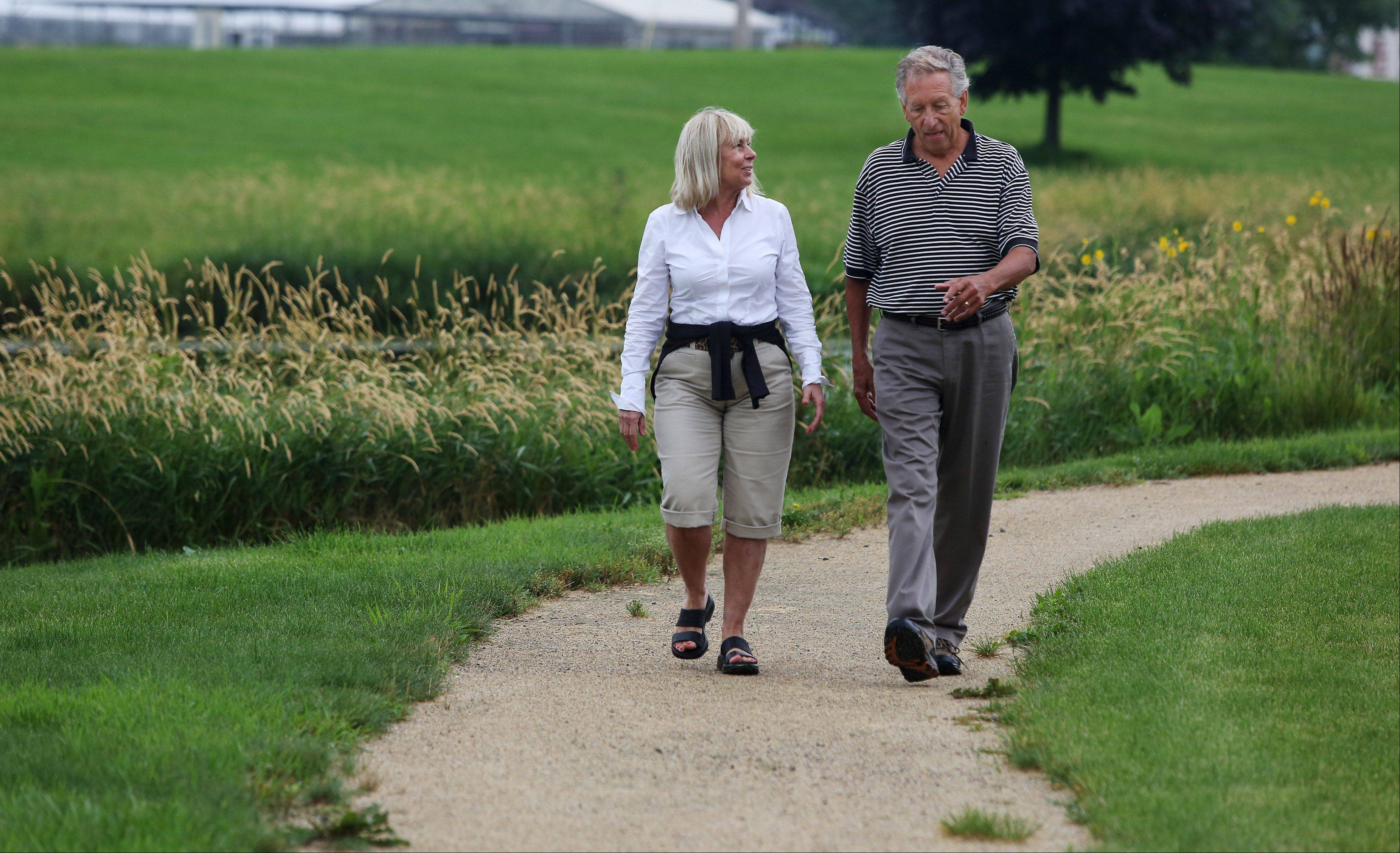 Mary Ann Andersen and Larry Waco Sr. walk along the many trails at Saddlebrook Farms in Grayslake.