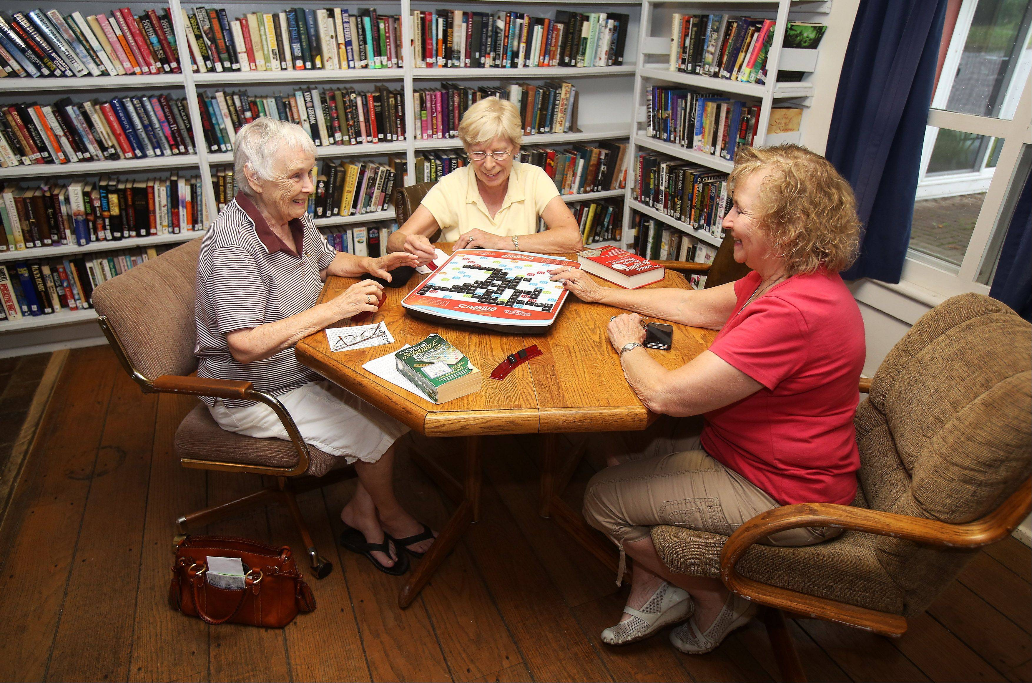 Jeri Schmidt, left, Helen Stumpf, and Sheila Buckman play Scrabble in the community center at Saddlebrook Farms in Grayslake.