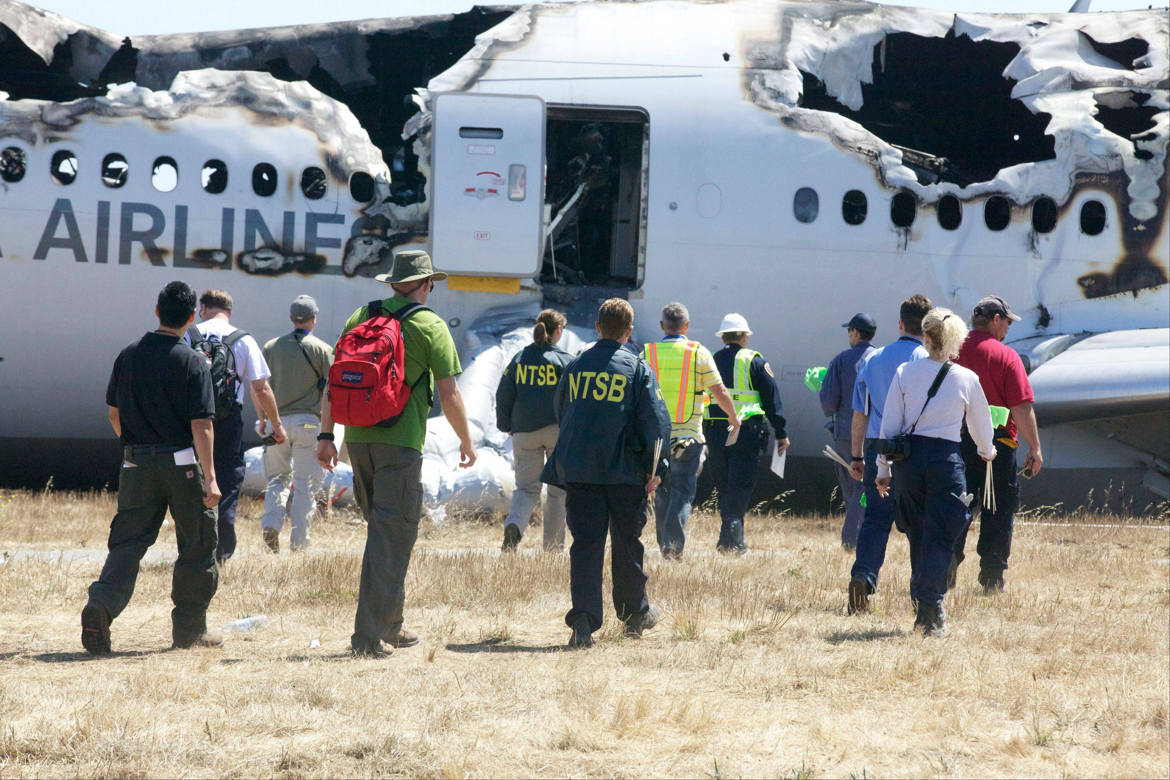 Investigators examine the wreckage at the scene of the Asiana Airline crash at San Francisco International Airport.
