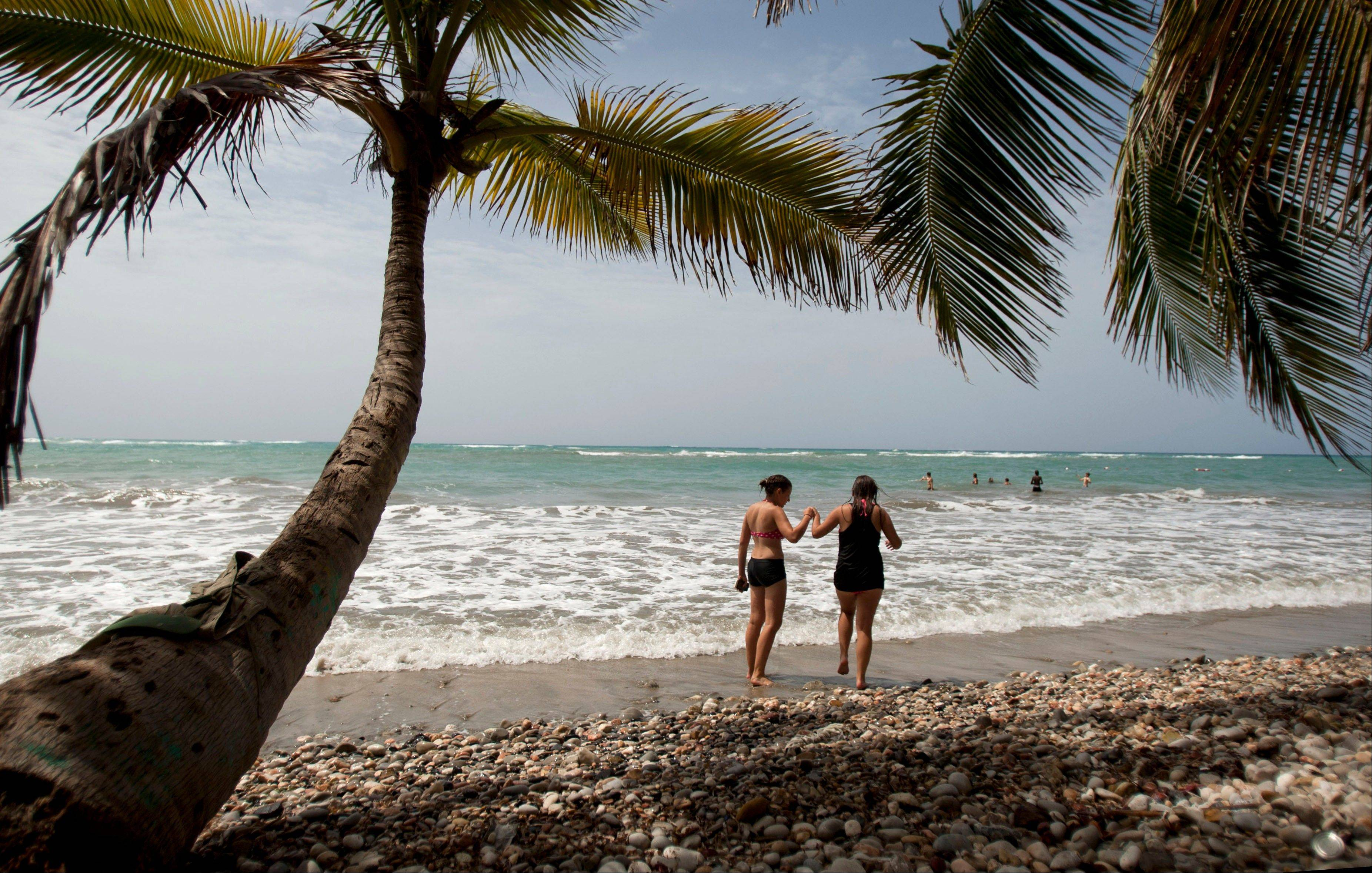 Tourists walk on the shore of the Raymond les bains beach in Jacmel, Haiti. The Haitian government is to trying to revive the country's long stagnant tourism industry with investments totaling more than $160 million.