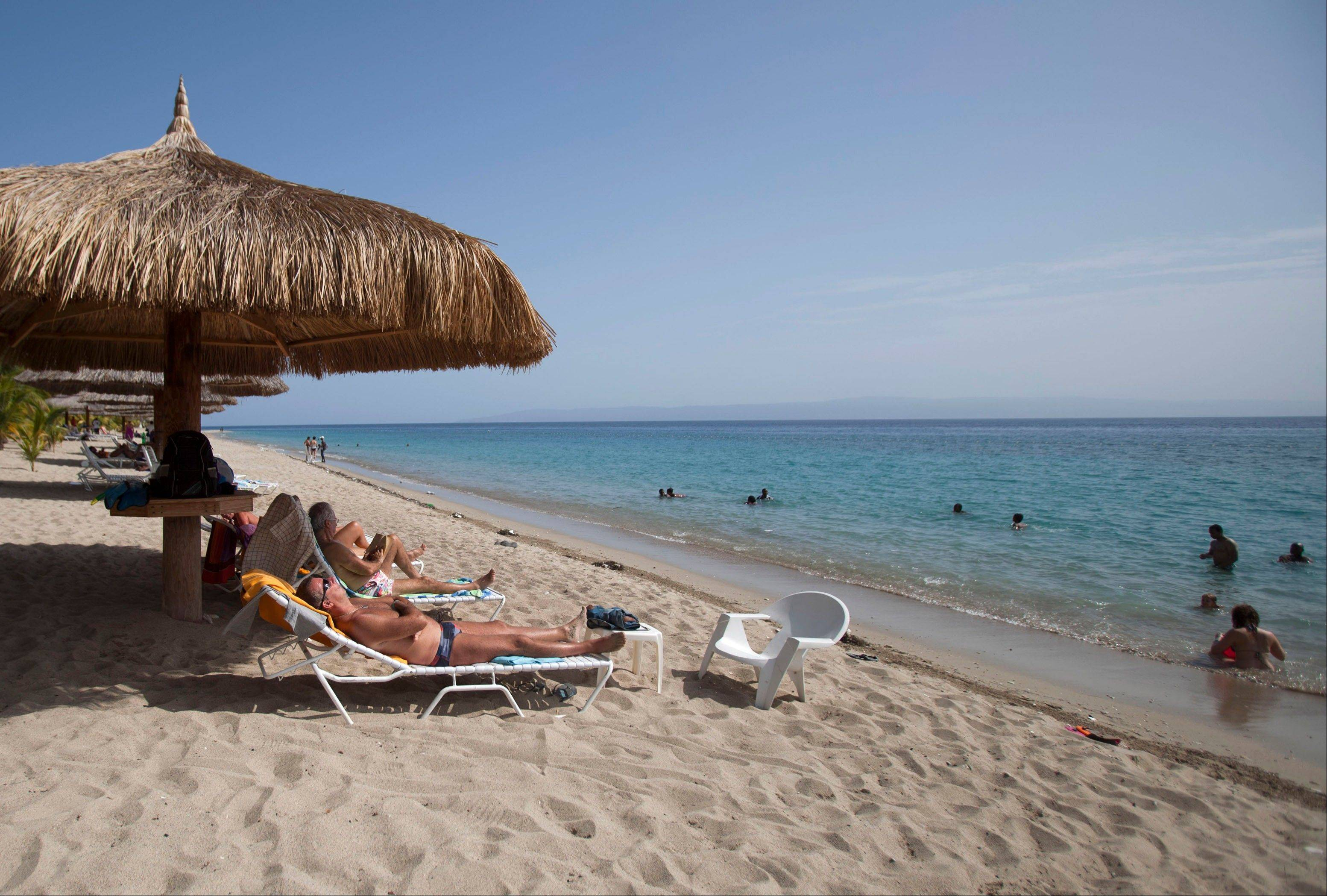 Tourists rest seaside while others wade in the ocean waters at the Club Indigo beach resort in Montrouis, Haiti.