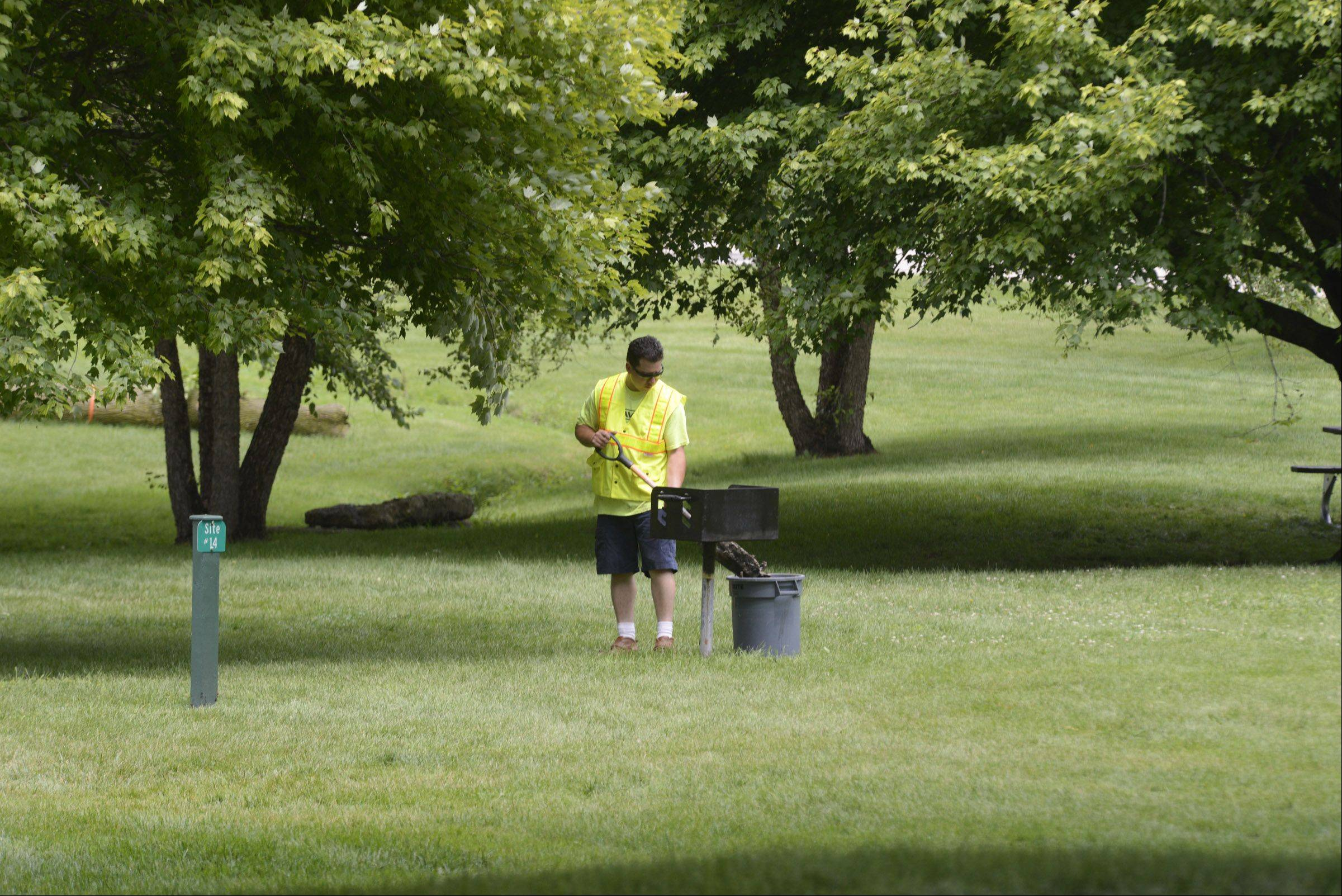 David Hernandez, of the Carpentersville Parks Department, cleans charcoal dust Monday from grills in Carpenter Park after a long holiday weekend. The park is undergoing a transformation of sorts, with several potentially diseased elm trees being removed, and a parking area being built.
