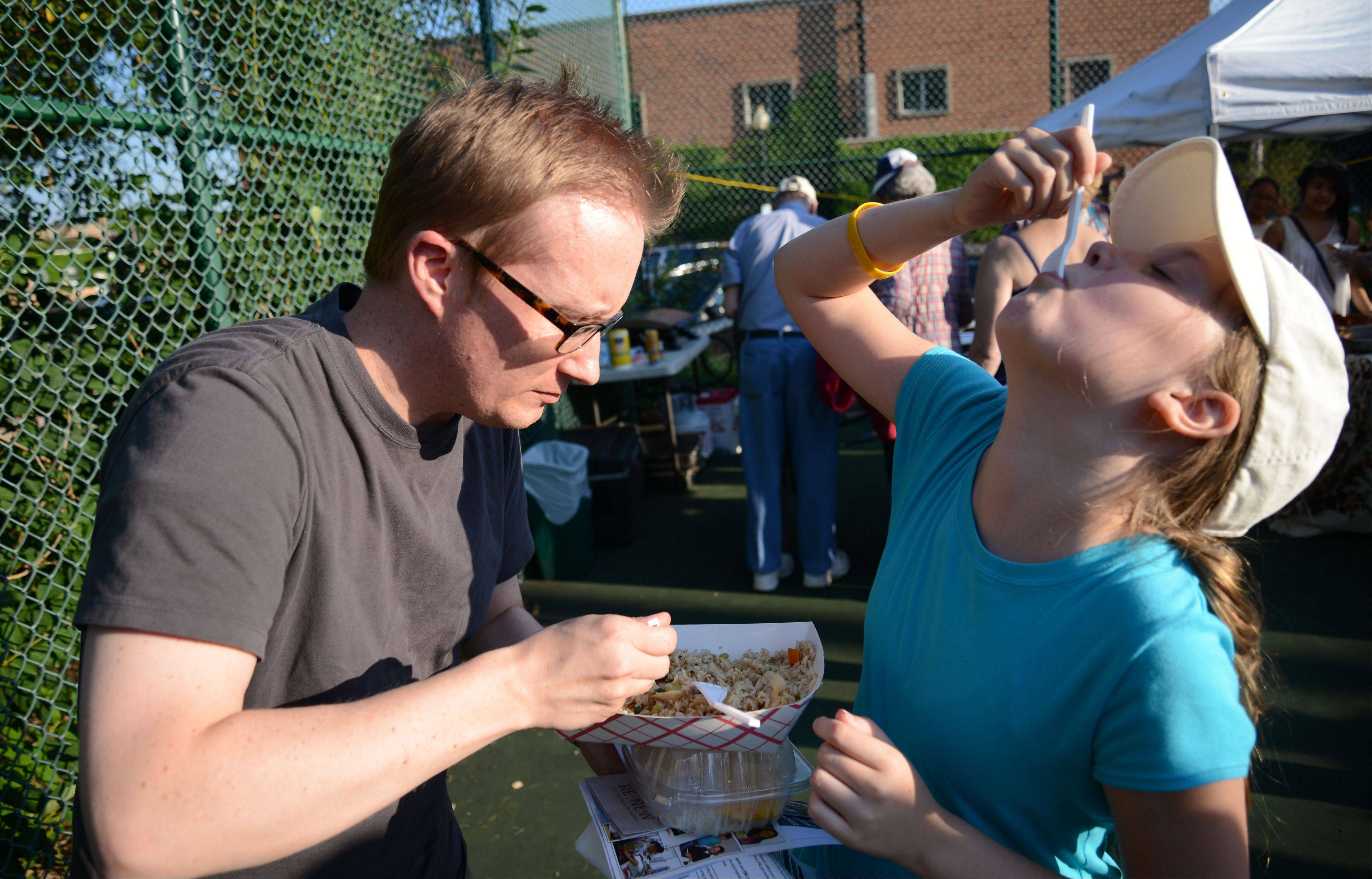 Ben Kopchick and his daughter Kathryn, 11, both of Wheaton, enjoy some fried rice at Wheaton World Tour at Memorial Park Thursday. More than 300 people attended the event that celebrated the culture within the community.
