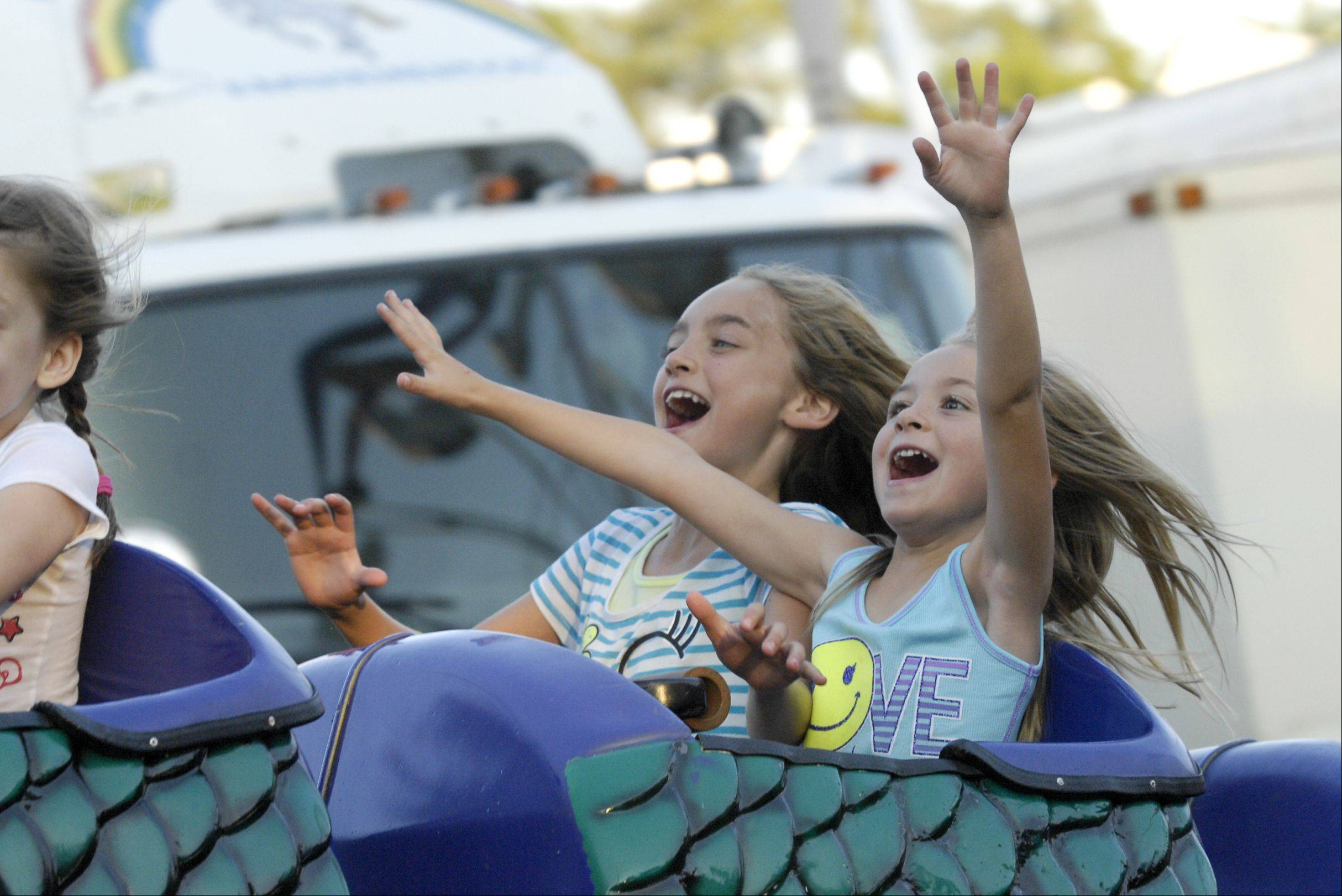 Bellastarr Jakresky, 9, and Jessie Ross, 5, of Roselle, ride the Dragon ride on the first day of the 2013 Itasca Fest, Thursday.