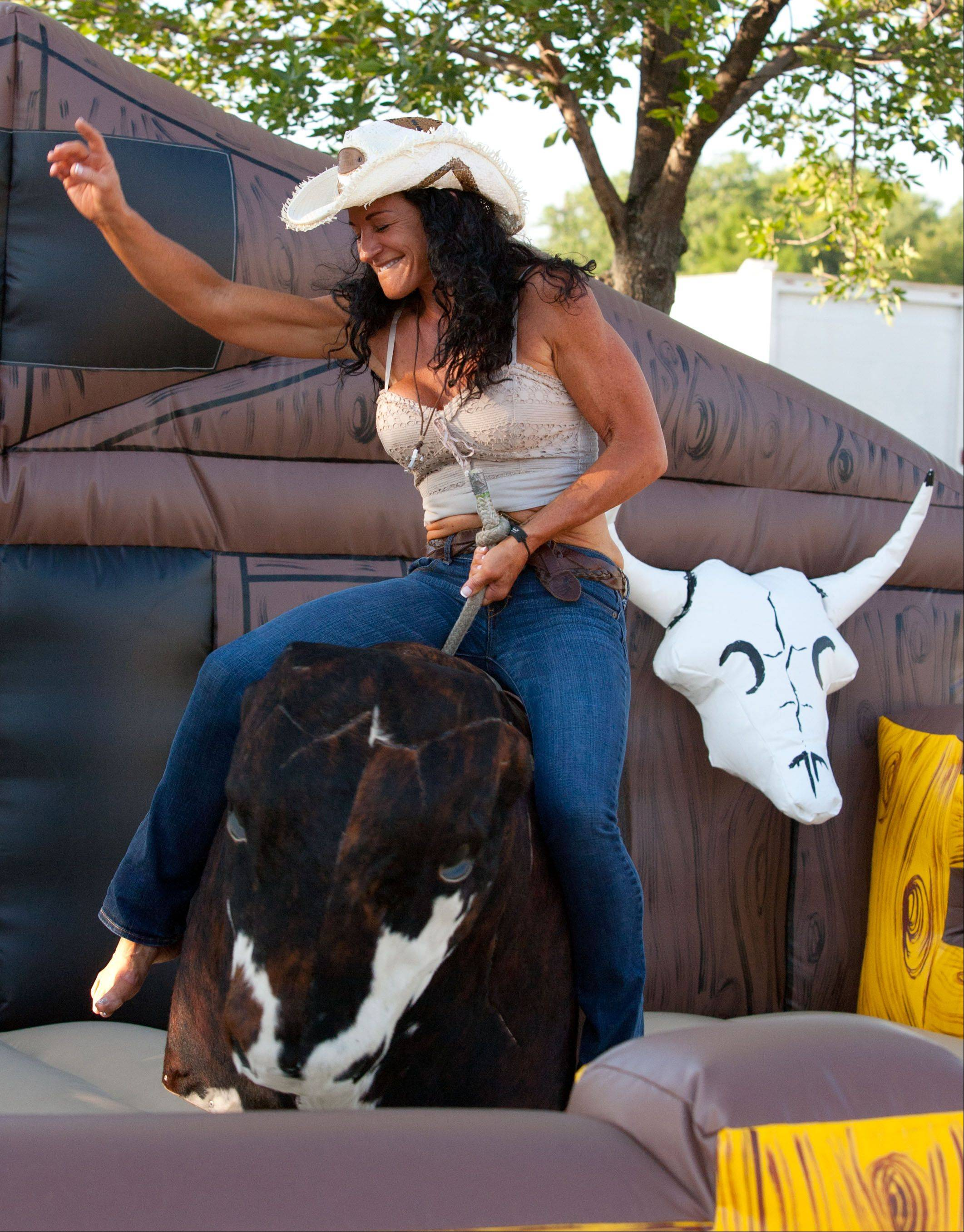 Karen Foresta of Addison rides the mechanical bull during country night at Glendale Heights Fest, in Camera Park.