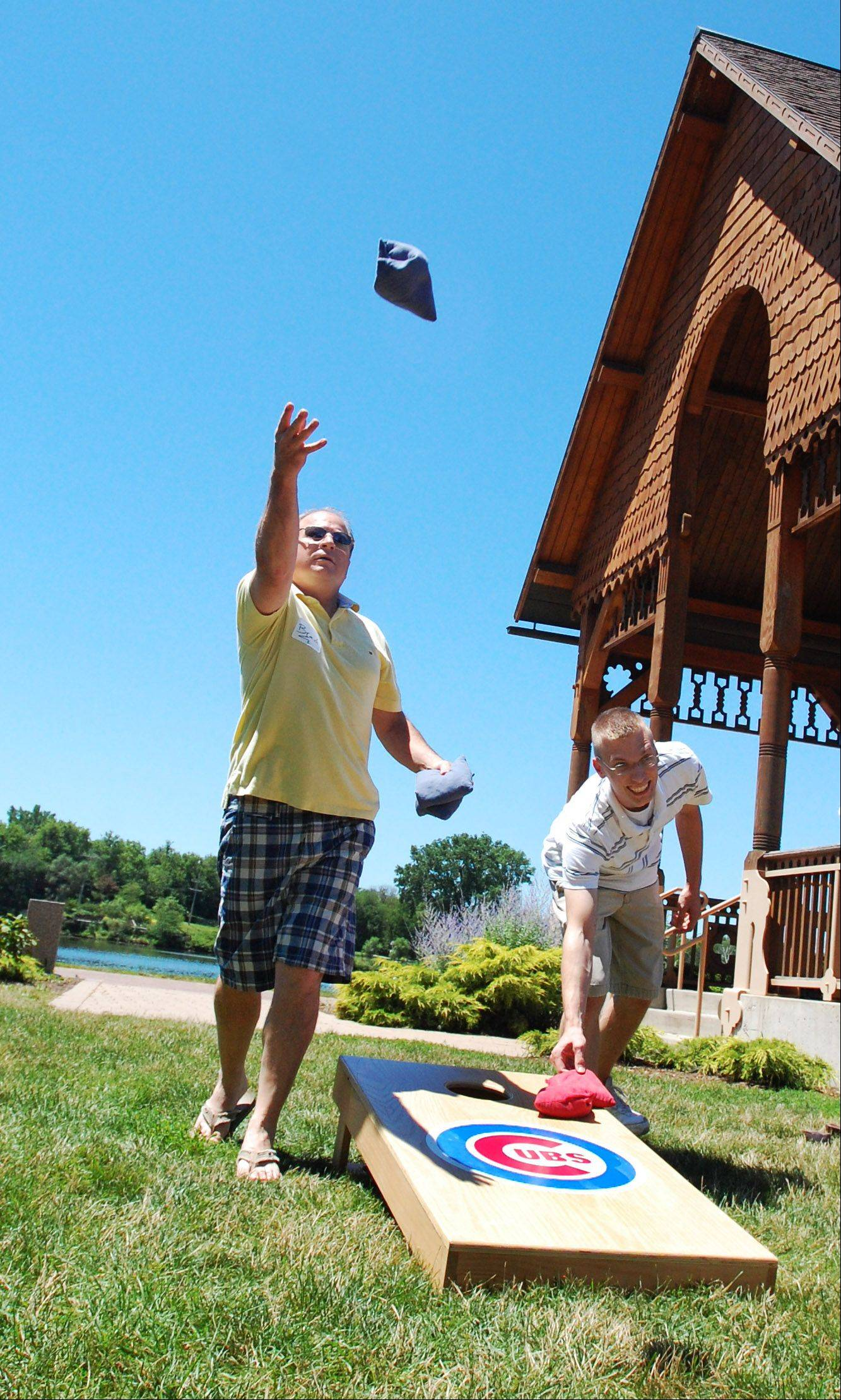 Brad McFall, left, of St. Charles, and Tom Kingsley, of Carol Stream, enjoy the beautiful weather and a game of bags at Pottawatomie Park on Friday. Aldi hosted a picnic for their employees, complete with music, games and catering from the Slow-Food Bar-B-Que truck.