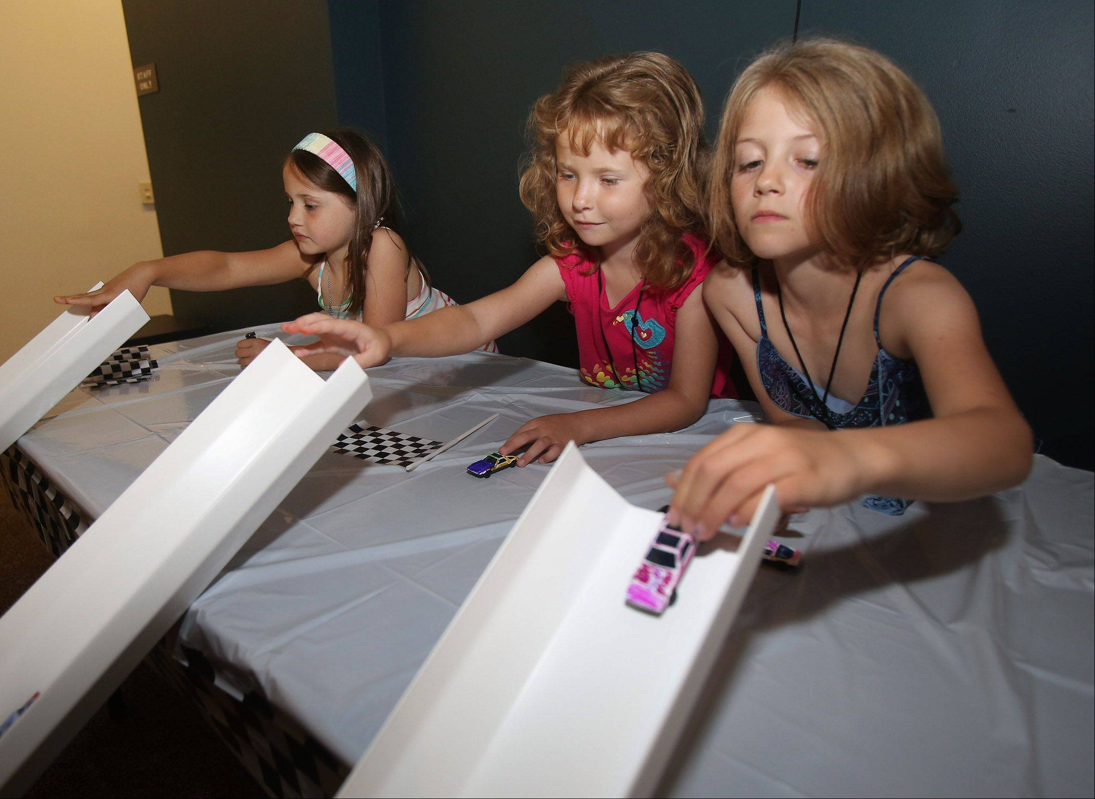 "Ellie Rebmann, 7, right, Abby Roddewig, 7, and Kelsey Nelson, 6, race their cars during the Race Car Rally Monday at the Wauconda Public Library. Children in grades 1-3 designed and raced cars on a track, received a drivers license, and ate ""auto parts"" snacks."