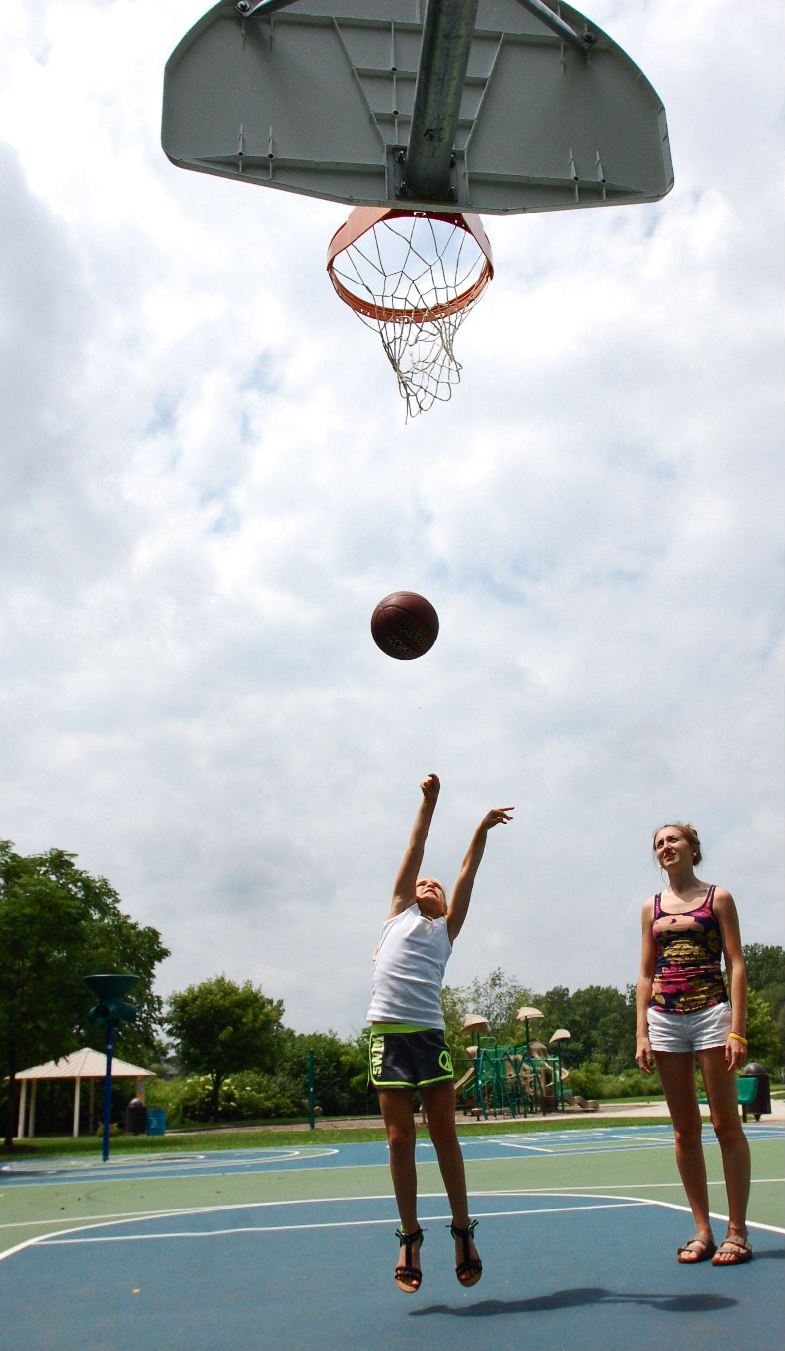 Christine Kelly, 8, of Geneva, and Jessica Theis, 20, of Batavia, play basketball at Braeburn Park in Batavia Monday.