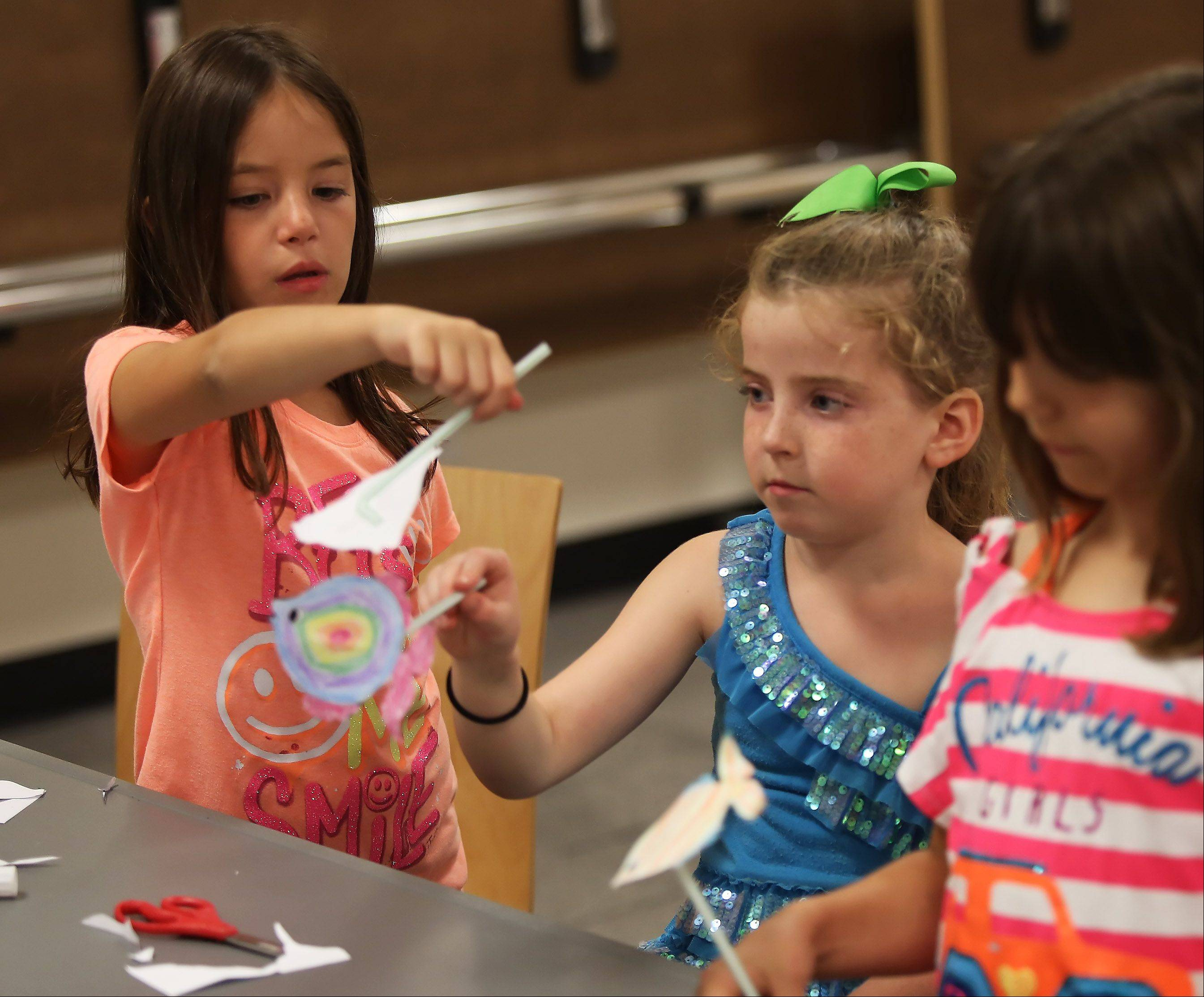 Seven-year-olds Zoe Joseph, left, and Ella Kennedy, both of Libertyville, play with the fish puppets they created during the puppet-making workshop Tuesday at the Cook Park Library in Libertyville. Children made shadow puppets and bag puppets under the direction of Mark Nichols, owner of The Puppet Place,