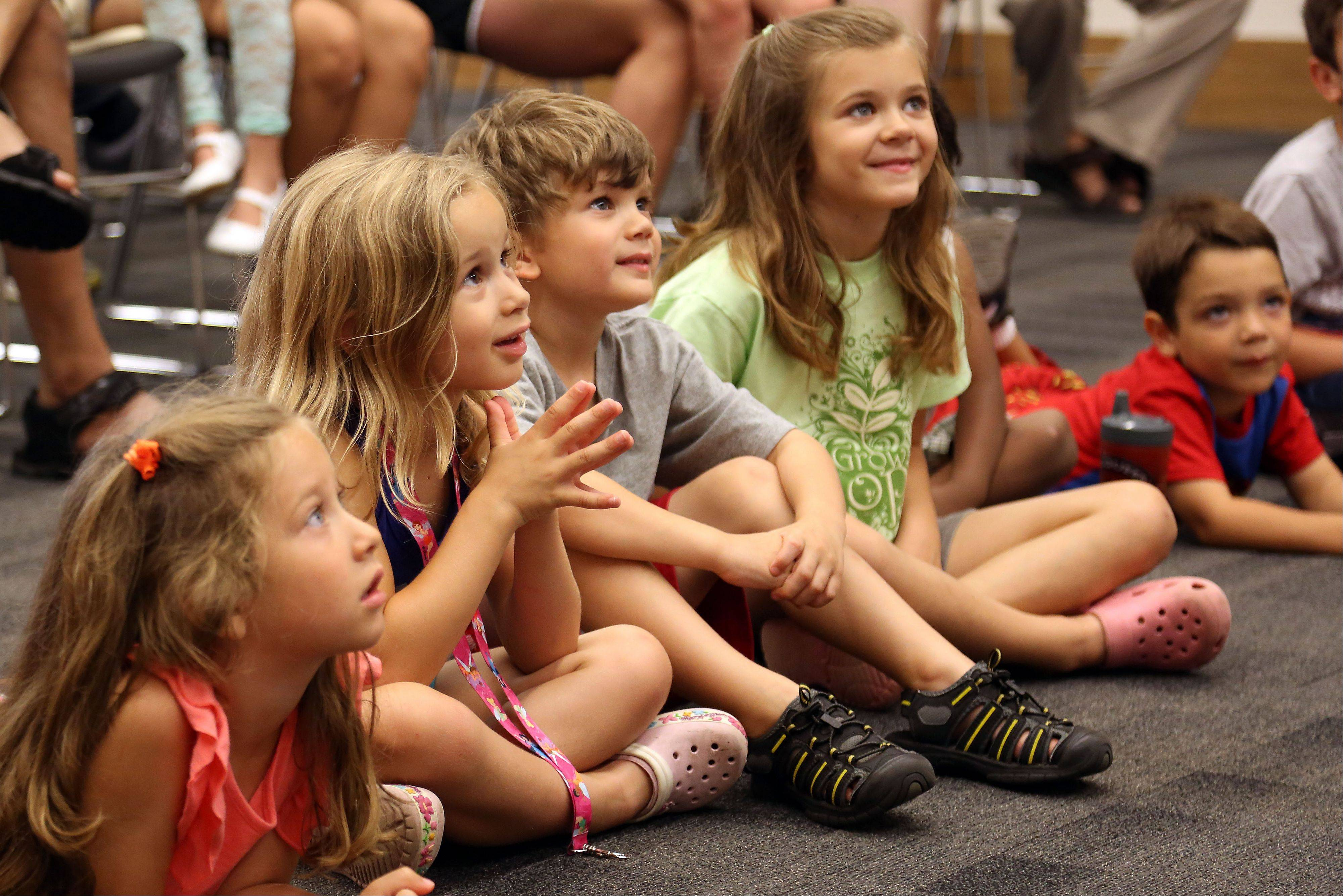 Kids listen intently as storyteller Anne Shimojima of Morton Grove tells Funny Stories from Around the World!, during a program at Warren-Newport Public Library in Gurnee Tuesday.