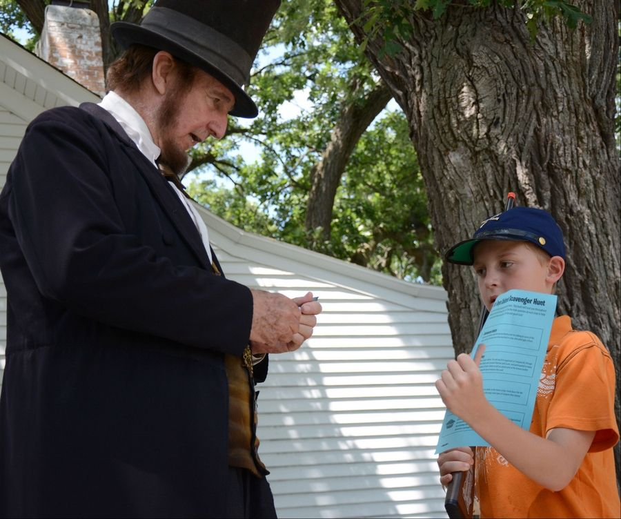 From right to left, Jaden Gausselin, 10, of Arlington Heights, asks for an autograph from Abe Lincoln, played by Max Daniels, of Wheaton, during at Civil War Days Sunday at the Lakewood Forest Preserve near Wauconda.