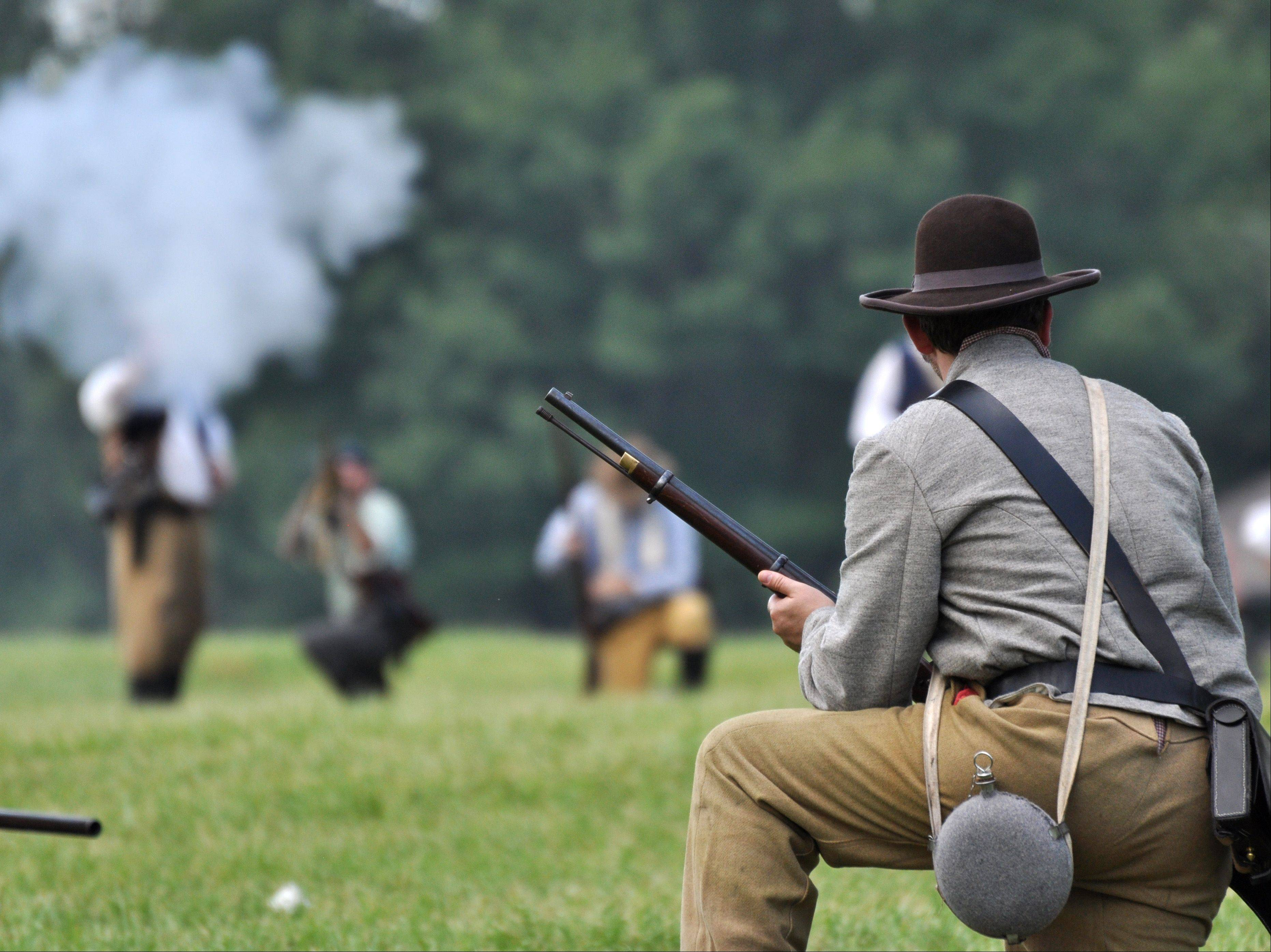 A Confederate soldier reloads as he is fired upon by the Union Army during a battle re-enactment Sunday at Civil War Days at the Lakewood Forest Preserve near Wauconda.