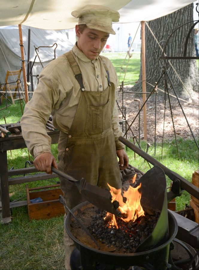 Sam Johnson, of Lakemoor, adds coals to his forge while explaining the process of blacksmithing to a gathering crowd Sunday at Civil War Days at the Lakewood Forest Preserve near Wauconda. Johnson has been blacksmithing for six years.