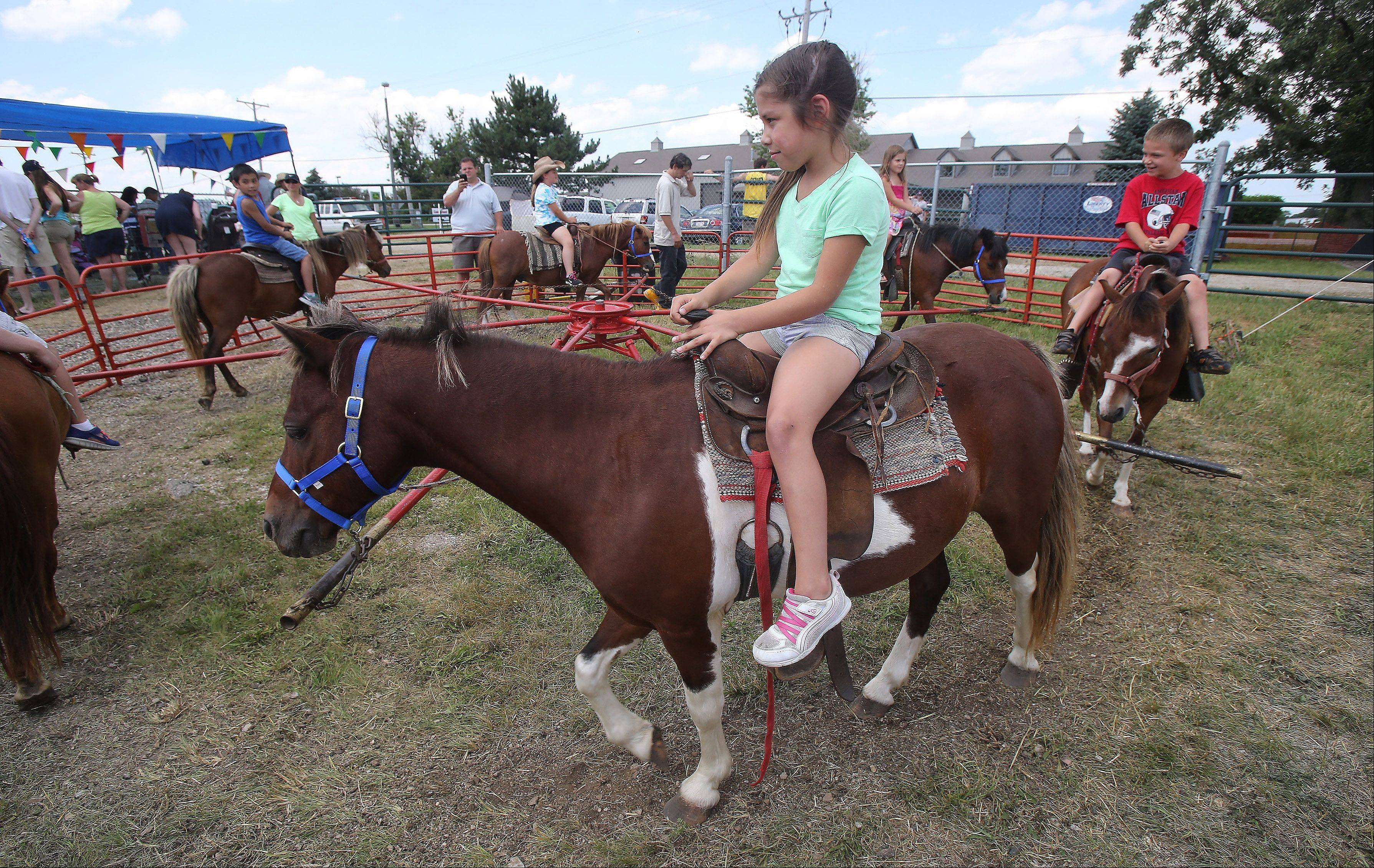 Nico Plumeri, 8, of Round Lake and her brother, Zac, 6, ride the ponies during the 50th Annual IPRA Championship Wauconda Rodeo Sunday at Green Oaks Rodeo Grounds. The Wauconda Area Chamber of Commerce sponsored the event that featured a mechanical bull, pony rides and calf roping as well as the rodeo show.
