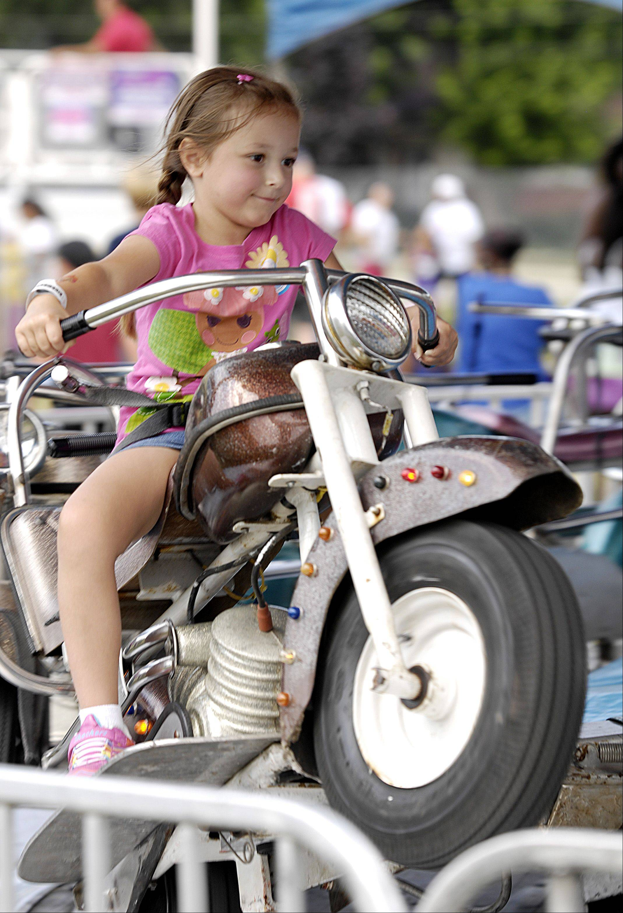 Mackenzie Clark, 5 of Itasca rides the Hampton Motorcycle ride during the final day of the 2013 Glendale Heights Fest, Sunday.