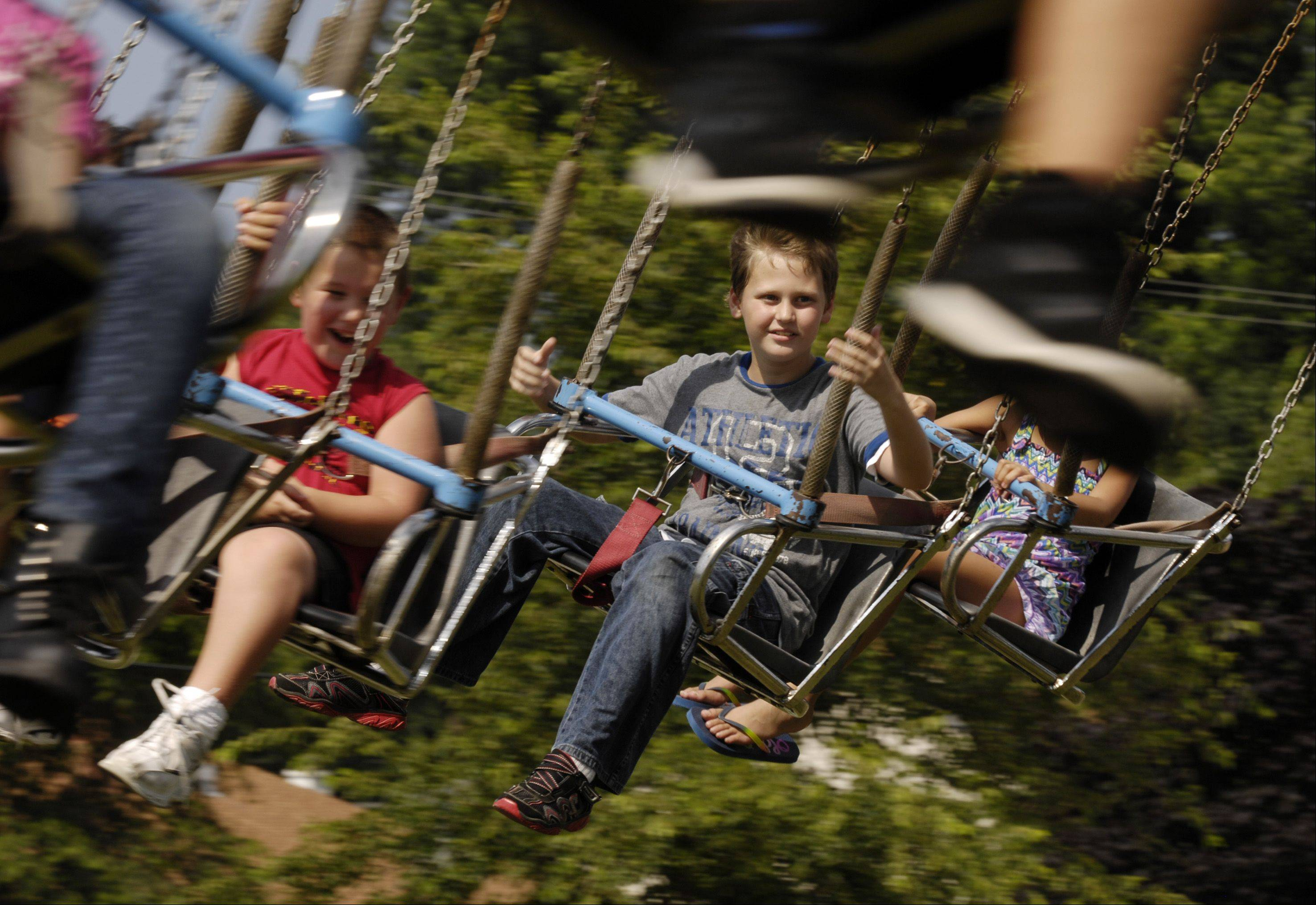 Mark Black/mblack@dailyherald.comChristian Myers, 13 of Carol Stream rides the YoYo swing ride during the final day of the 2013 Glendale Heights Fest, Sunday.
