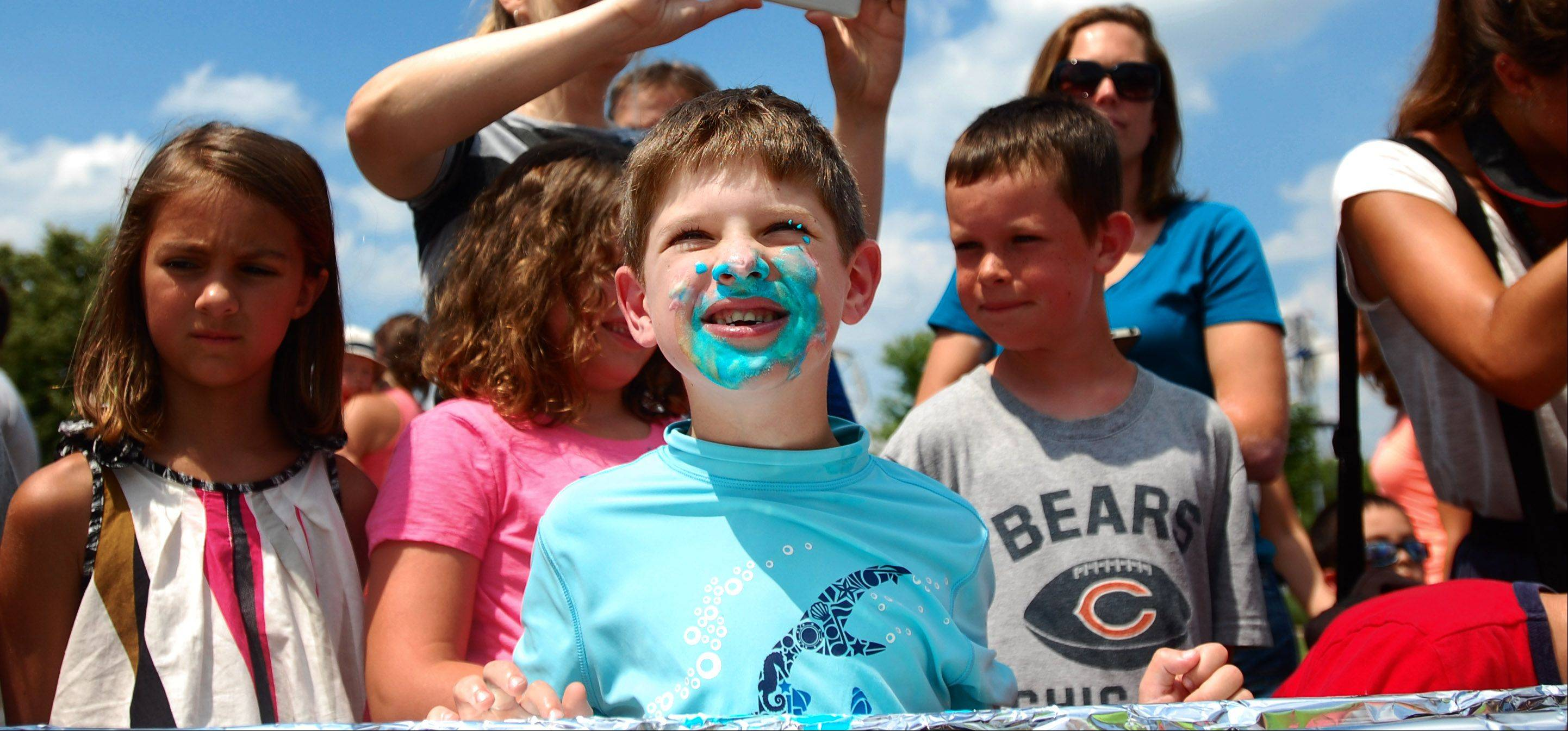 "Joe Schroeder, 6, of Batavia emerges from his ice cream smiling at his family after completing the ""Get your Mind in the Gutter"" Ice cream eating contest. The contest was held at the Windmill City Festival on Sunday, July 14 at the Riverwalk in Batavia."