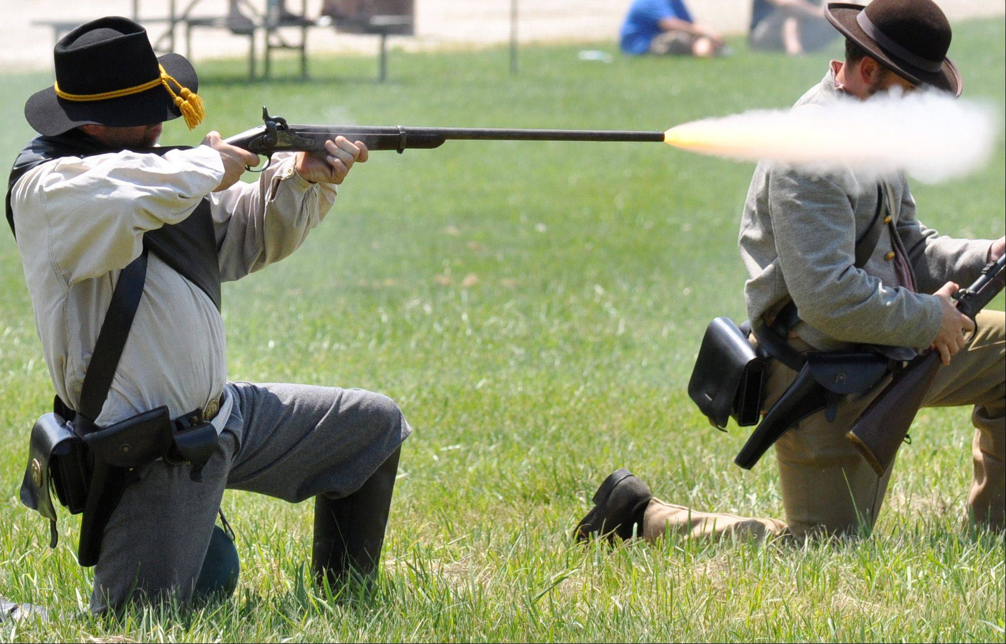 A confederate soldier fires upon the Union Calvary during a battle re-enactment at Civil War Days held at the Lakewood Forest Preserve Sunday, July 14.