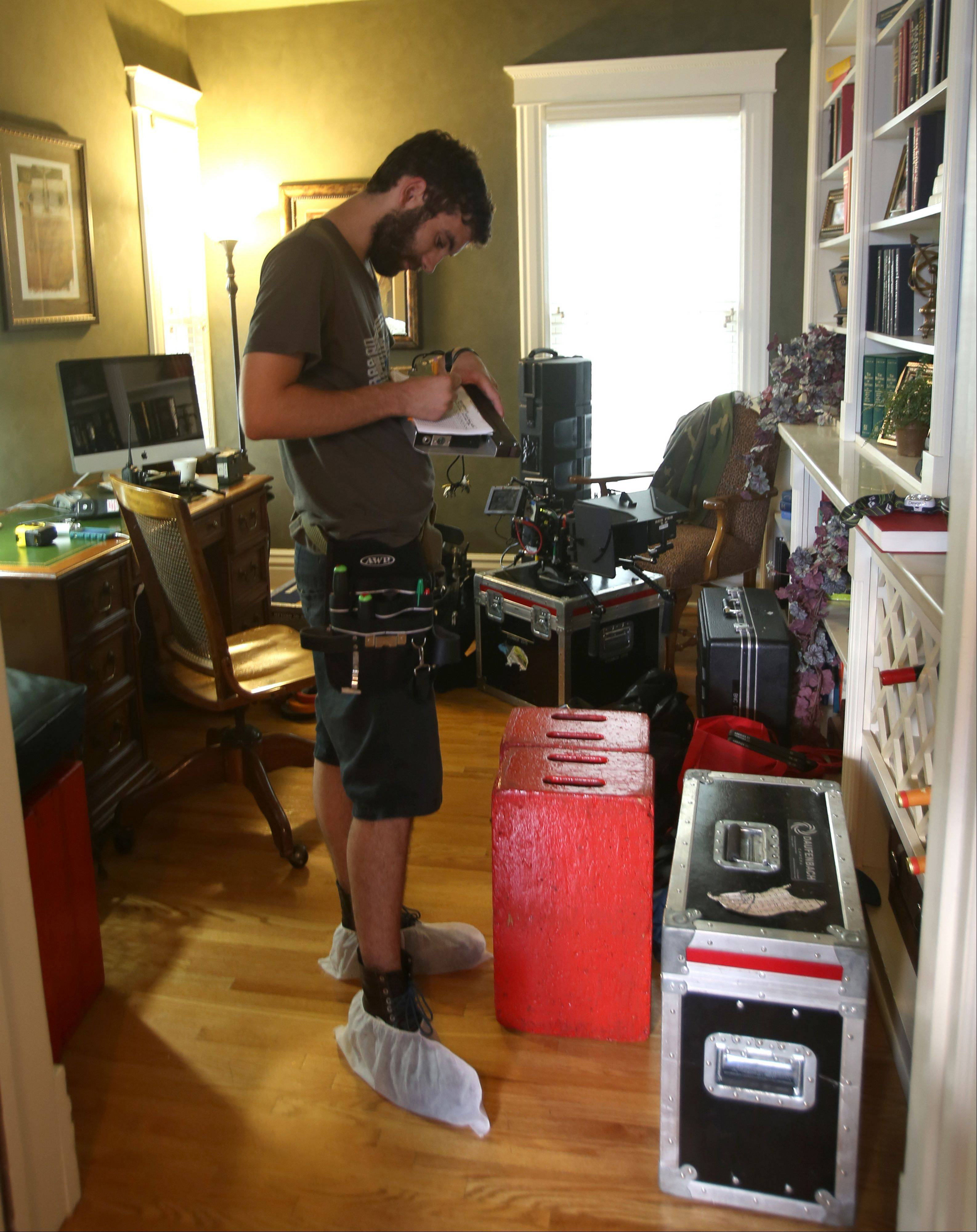 "Cameraman Adam LoNigro records data between scene shots of the movie ""Precious Mettle"" at a home in downtown Naperville last month."