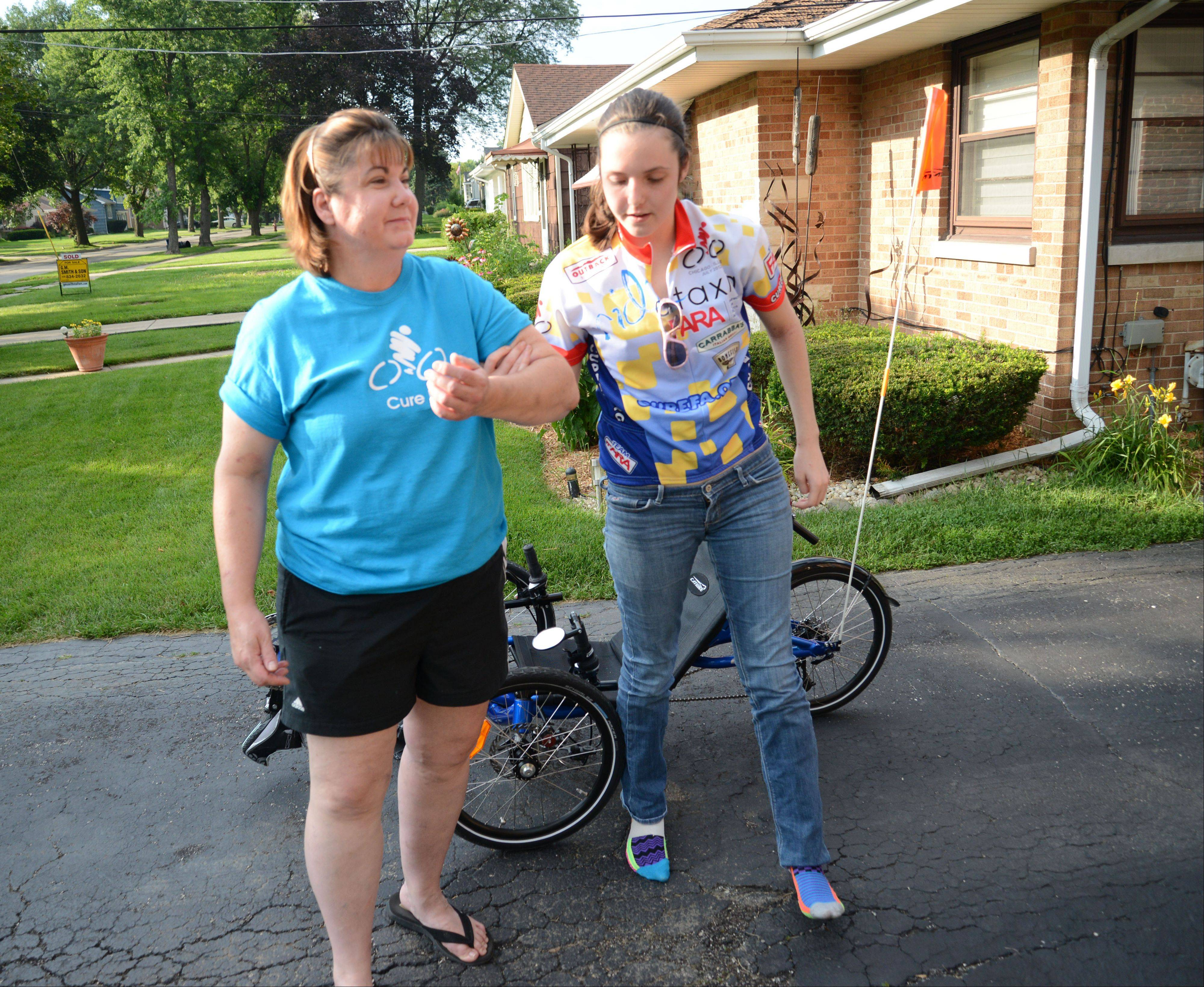 Always there to offer support when needed, Kelly Kramer helps her daughter, Nicole Kramer, back to their Villa Park home after the teen finishes a ride on her new custom cycle. The 19-year-old suffers from Friedreich's ataxia, an incurable neurological disorder.