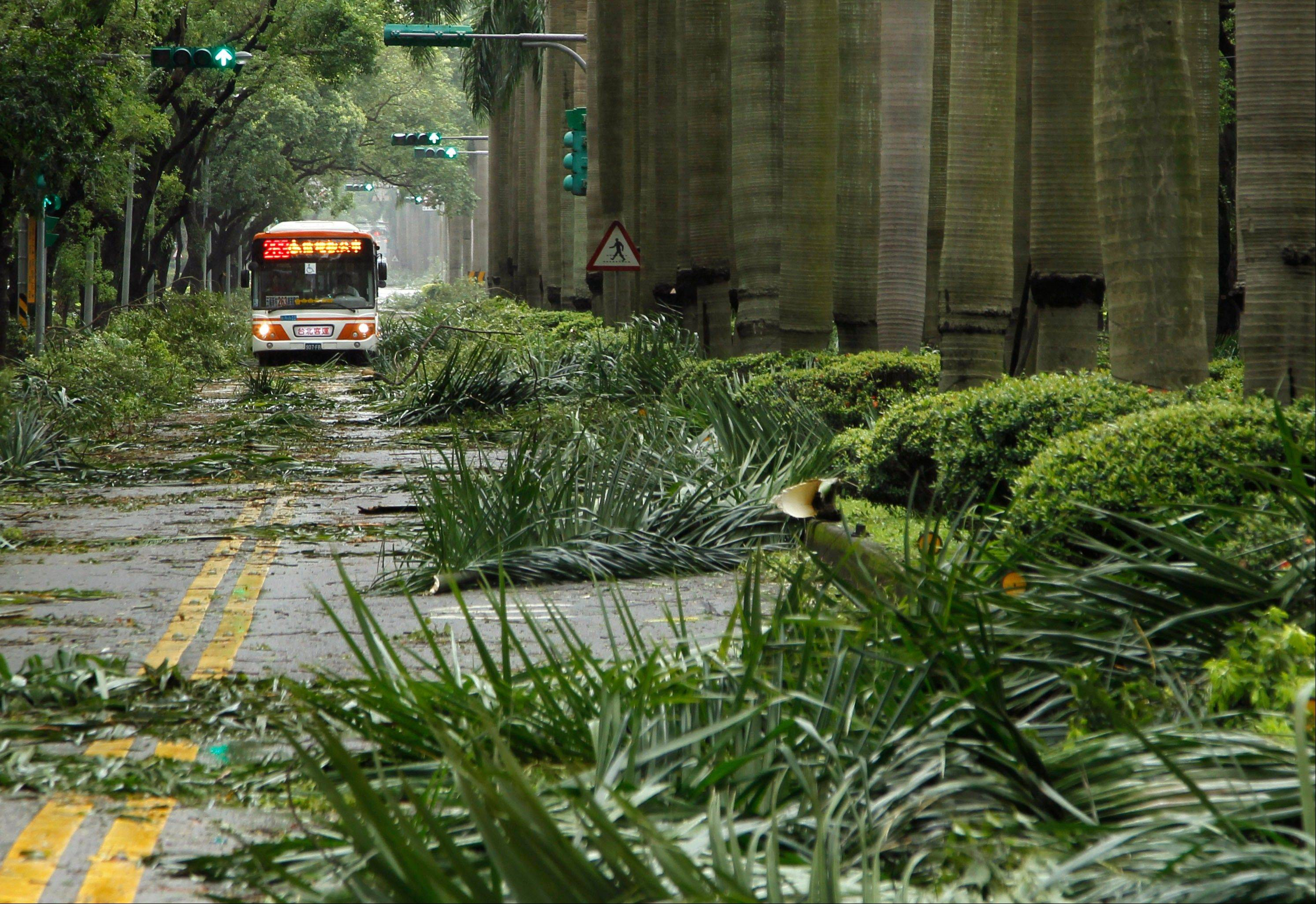 A public bus maneuvers through a path of debris from strong winds of Typhoon Soulik early Saturday, in Taipei, Taiwan.