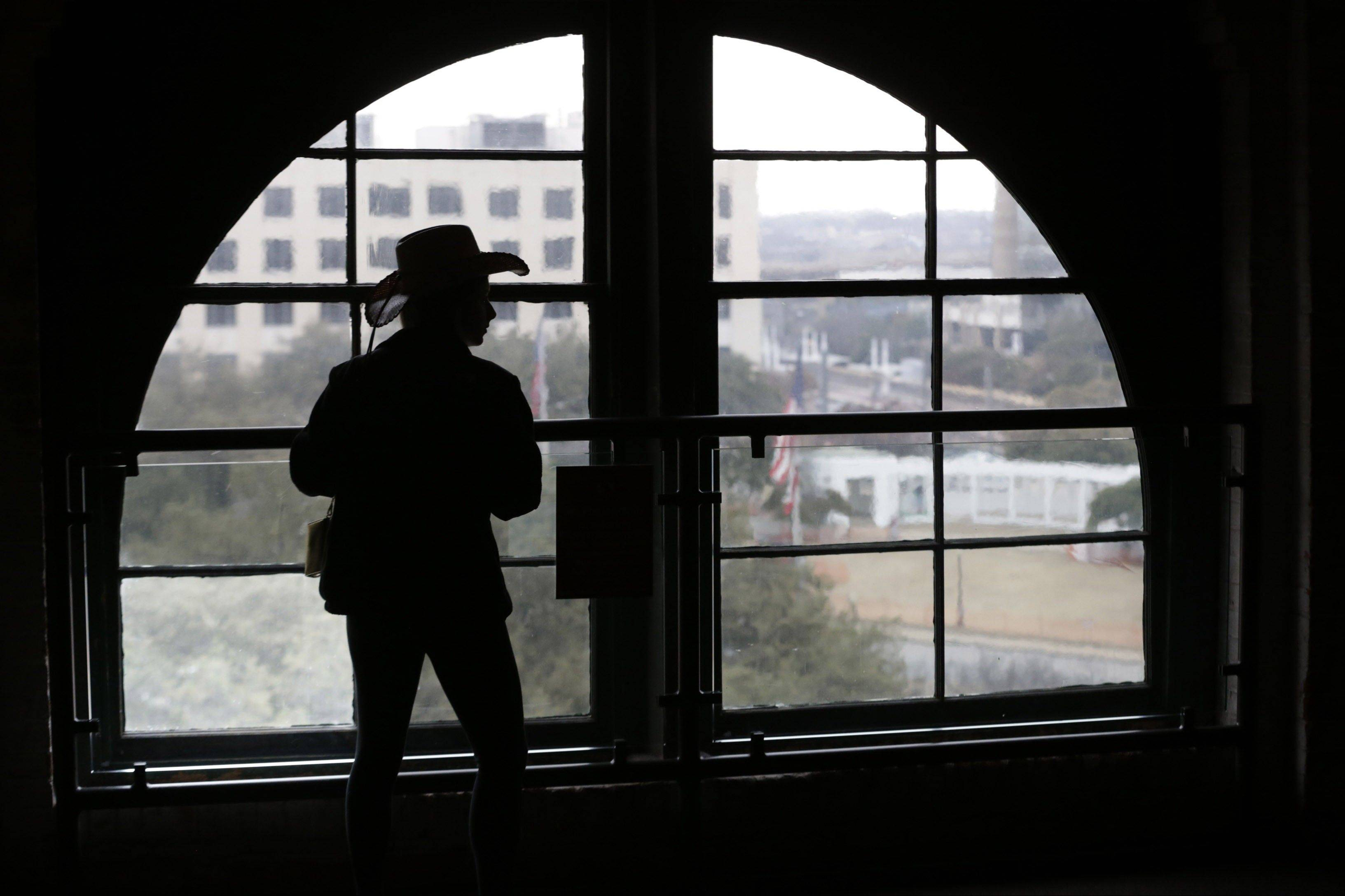 In this photo made Friday, Jan. 25, 2013, a visitor wearing a cowboy hat looks out onto Dealey Plaza from the Sixth Floor Museum located in the former Texas School Book Depository building in Dallas. As the nation and world mark the 50th anniversary this year of the assassination of John F. Kennedy, special attention once again falls on Dallas.