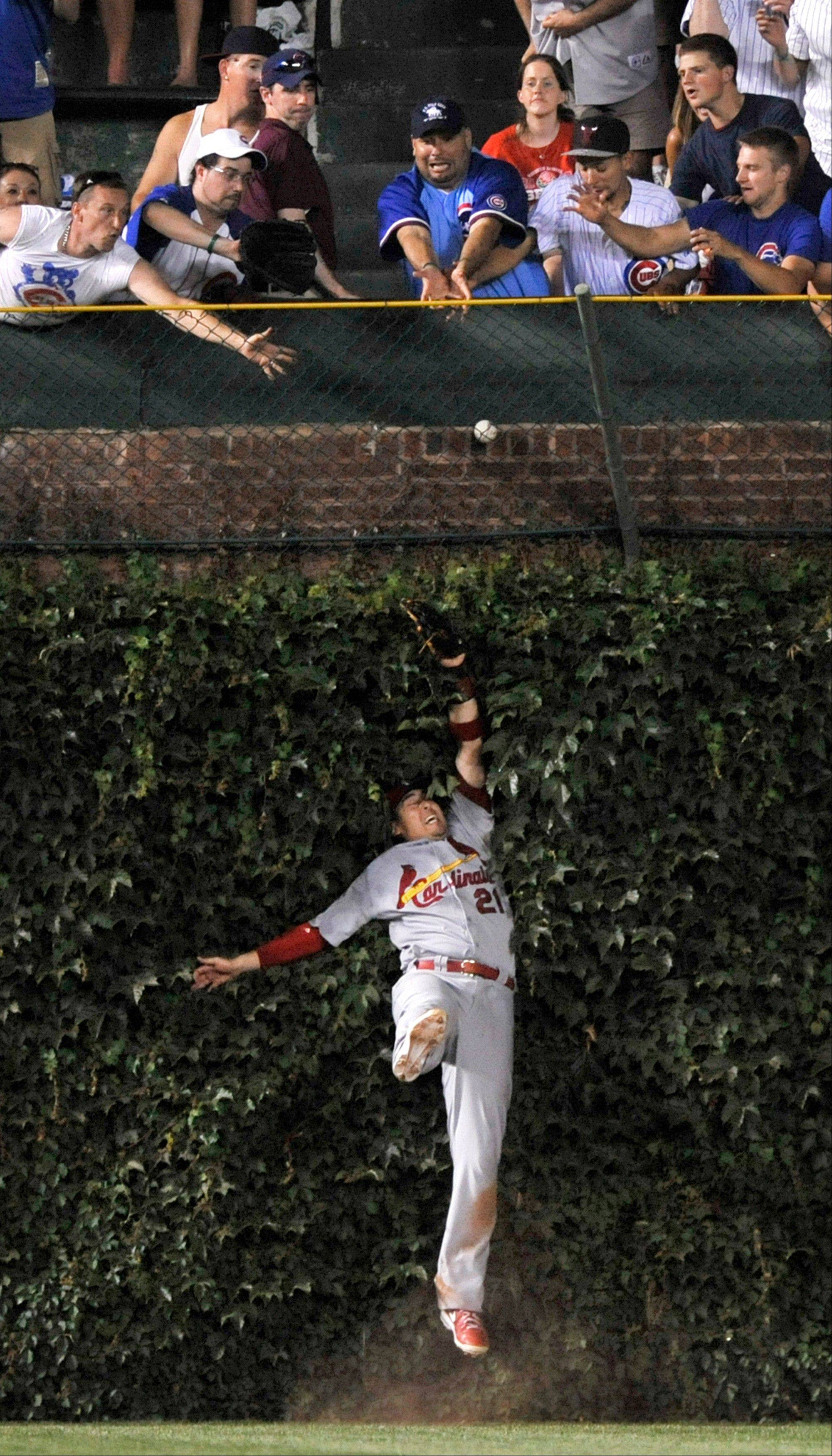 St. Louis Cardinals left fielder Allen Craig attempts to catch a three-run home run hit by the Cubs' Darwin Barney during the sixth inning of a baseball game in Chicago, Sunday, July 14, 2013.