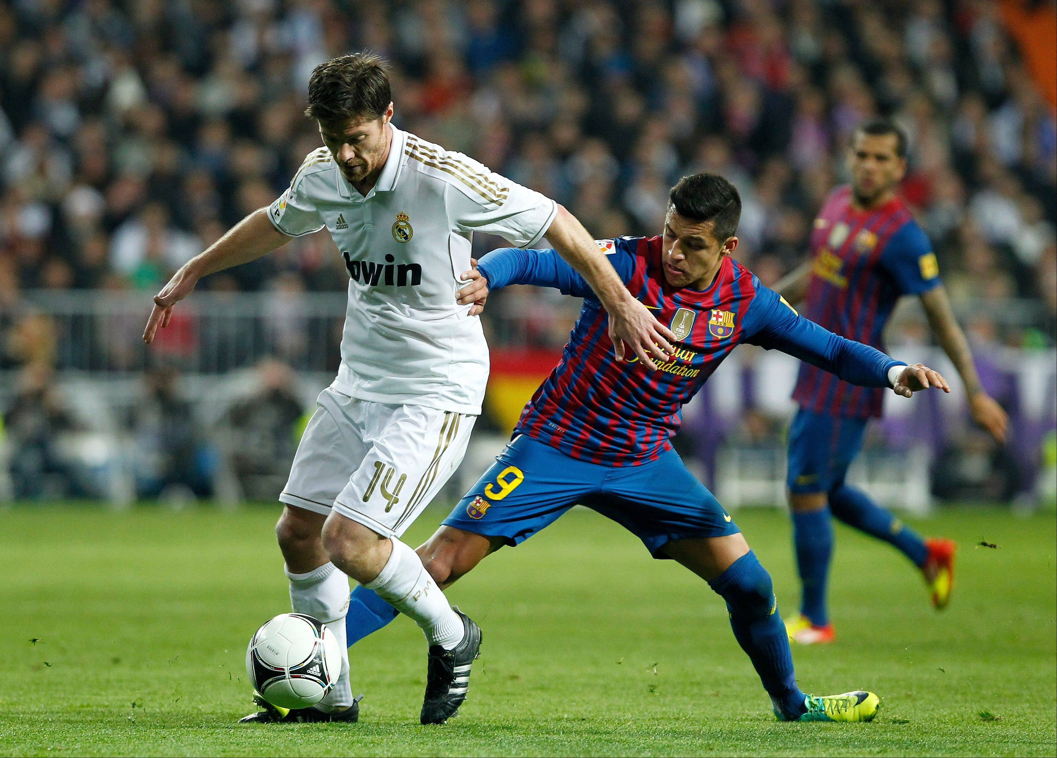FC Barcelona's Alexis Sanchez from Chile, right, vies for the ball with Real Madrid's Xabi Alonso, left, during a match in Madrid, Spain, in January 2012. Forbes said Monday that Real Madrid is the most valuable sports team in the world.