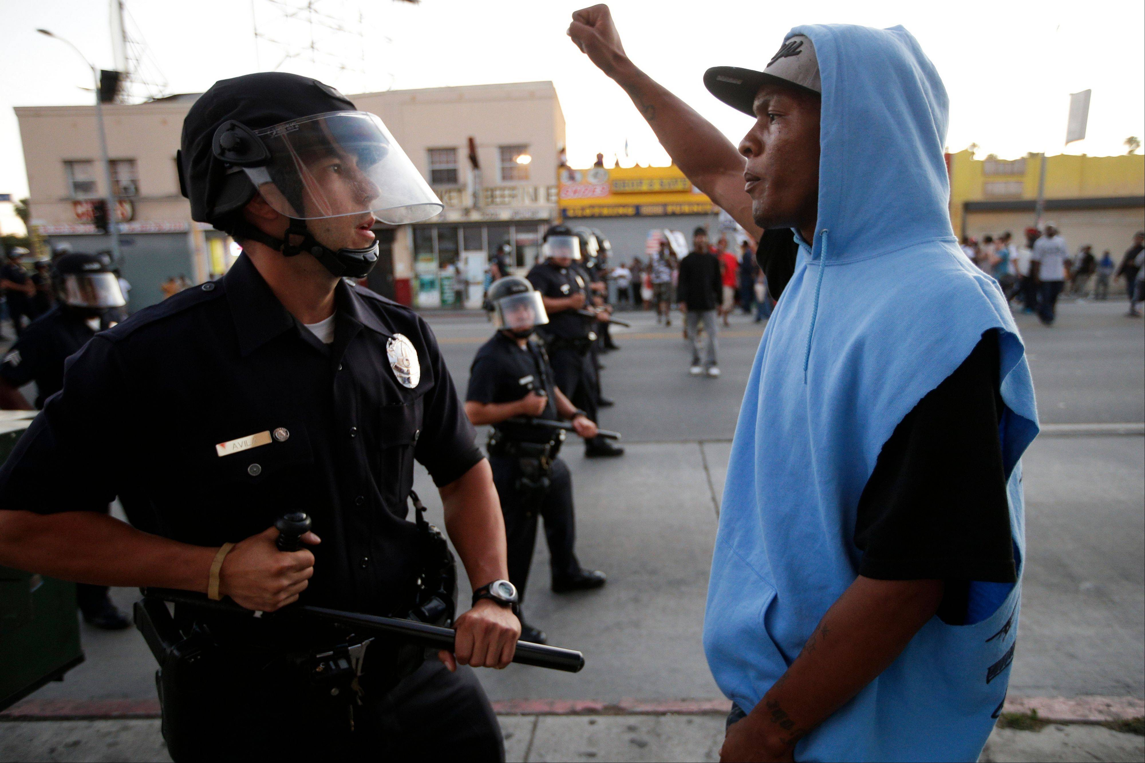 A protester confronts a Los Angles police officer Monday during a demonstration in reaction to the acquittal of neighborhood watch volunteer George Zimmerman.