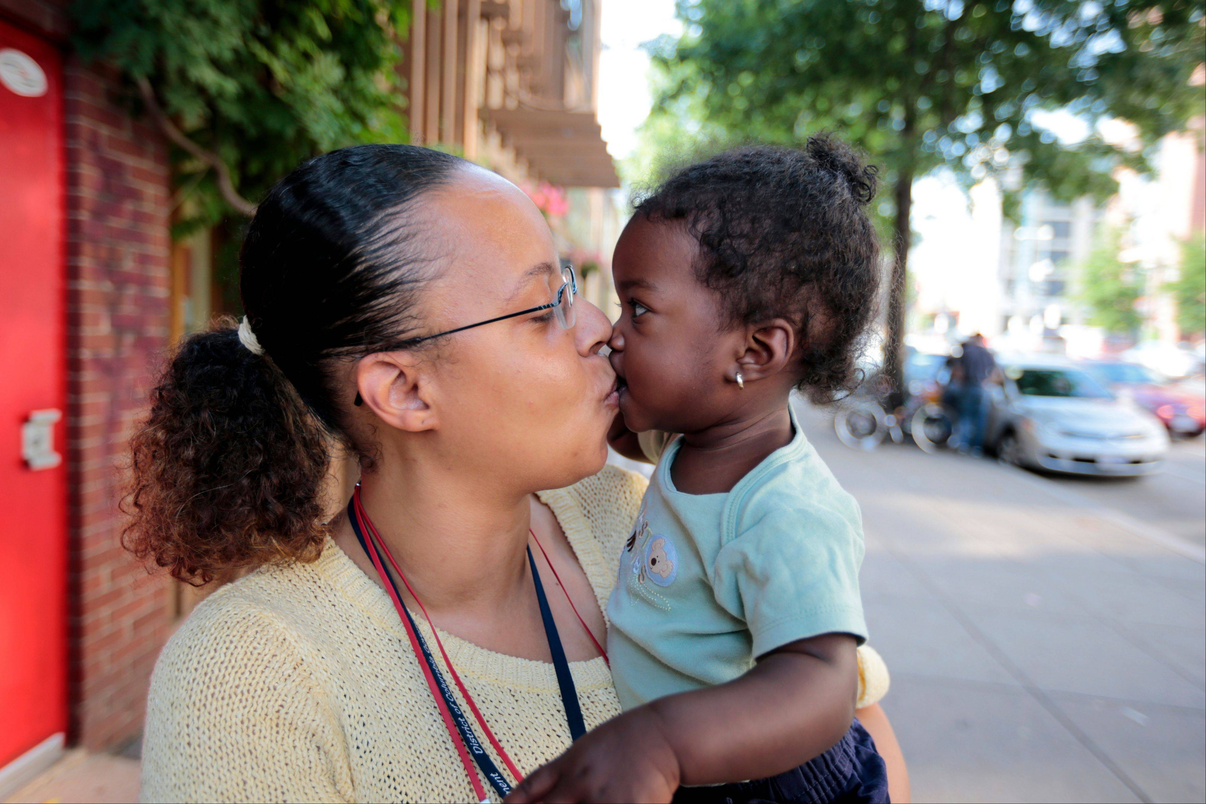 Ke�sha Scrivner, left, kisses her daughter as they pose for a photograph after picking up her daughter Ka�Lani Scrivner, 1, from day care, Tuesday, July 9, 2013, in Washington. Once on welfare, Scrivner worked her way off by studying early childhood education and landing a full-time job for the District of Columbia�s education superintendent. She sees education as the path to a better life for herself and all five of her children, pushing them to finish high school and continue with college or a trade school.
