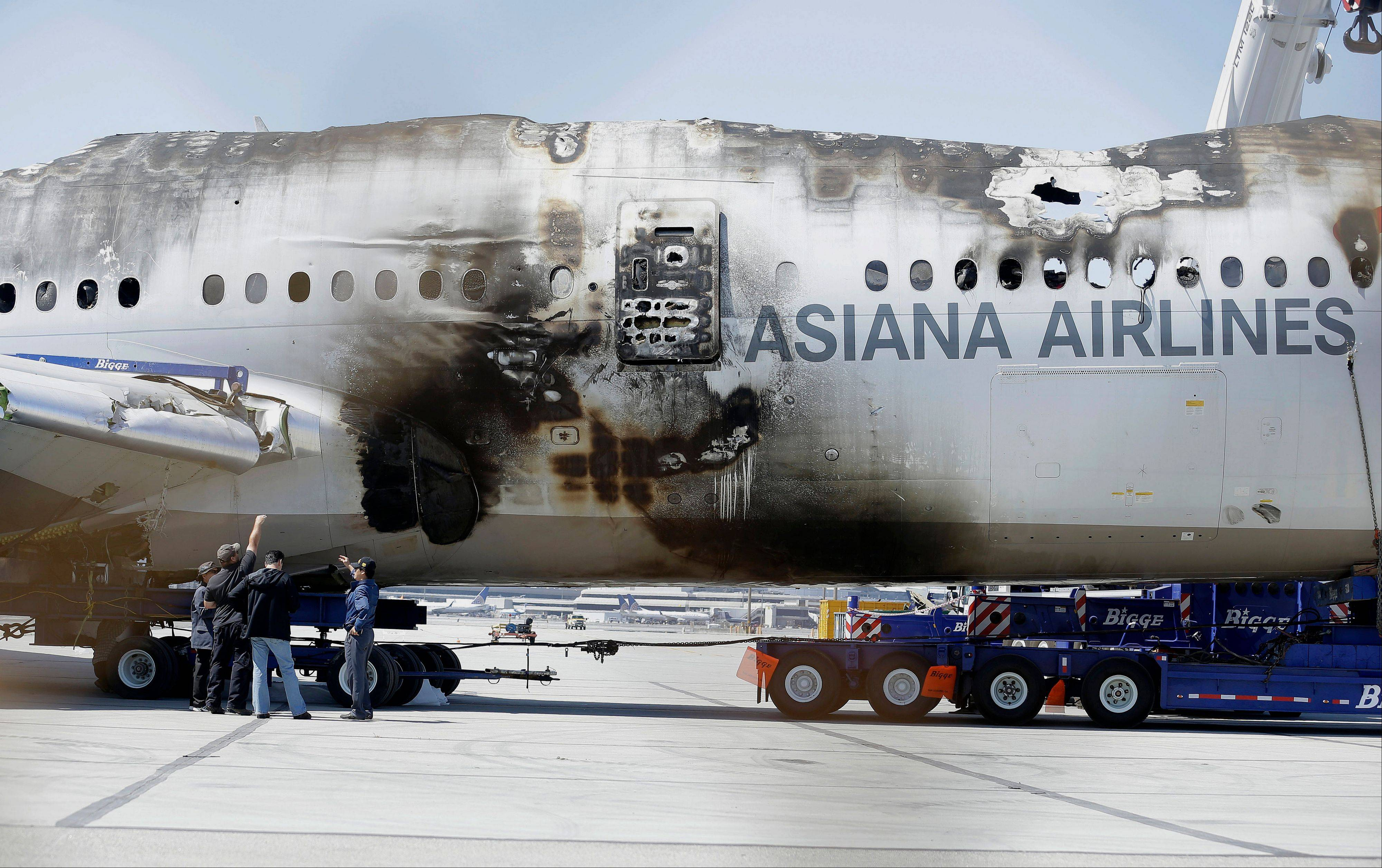 A group of men look at the wreckage of Asiana Flight 214, which crashed on July 6, at San Francisco International Airport. siana announced Monday that it will sue a San Francisco TV station that it said damaged the airline's reputation by using bogus and racially offensive names for four pilots on a plane that crashed earlier this month in San Francisco.
