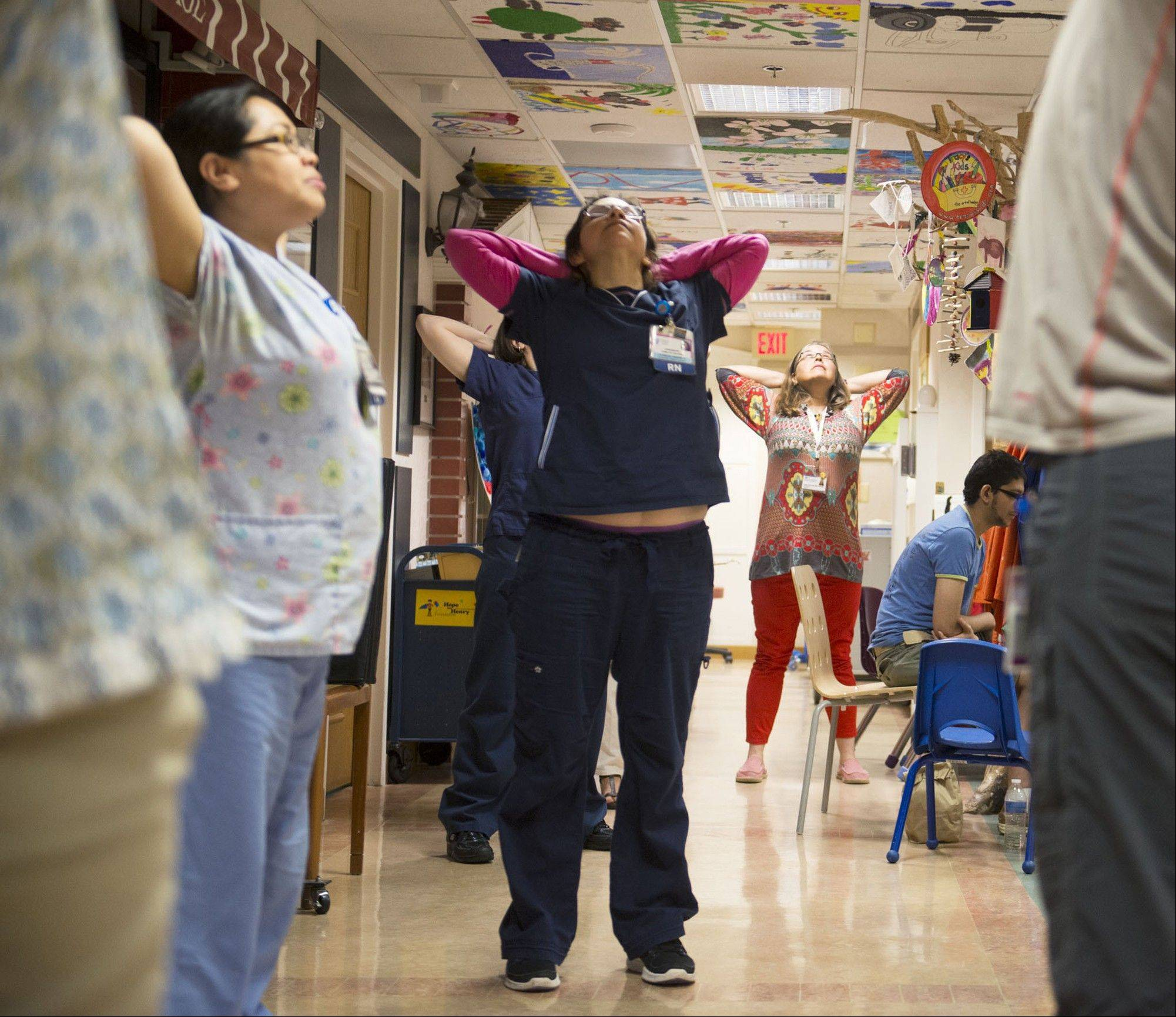 Nurses receive some stretching exercises from Daniel Burkholder, right, inside the Georgetown Lombardi Comprehensive Cancer Center. Medical institutions are implementing programs to help both patients and staffers learn to cope with stress and promote staff morale.