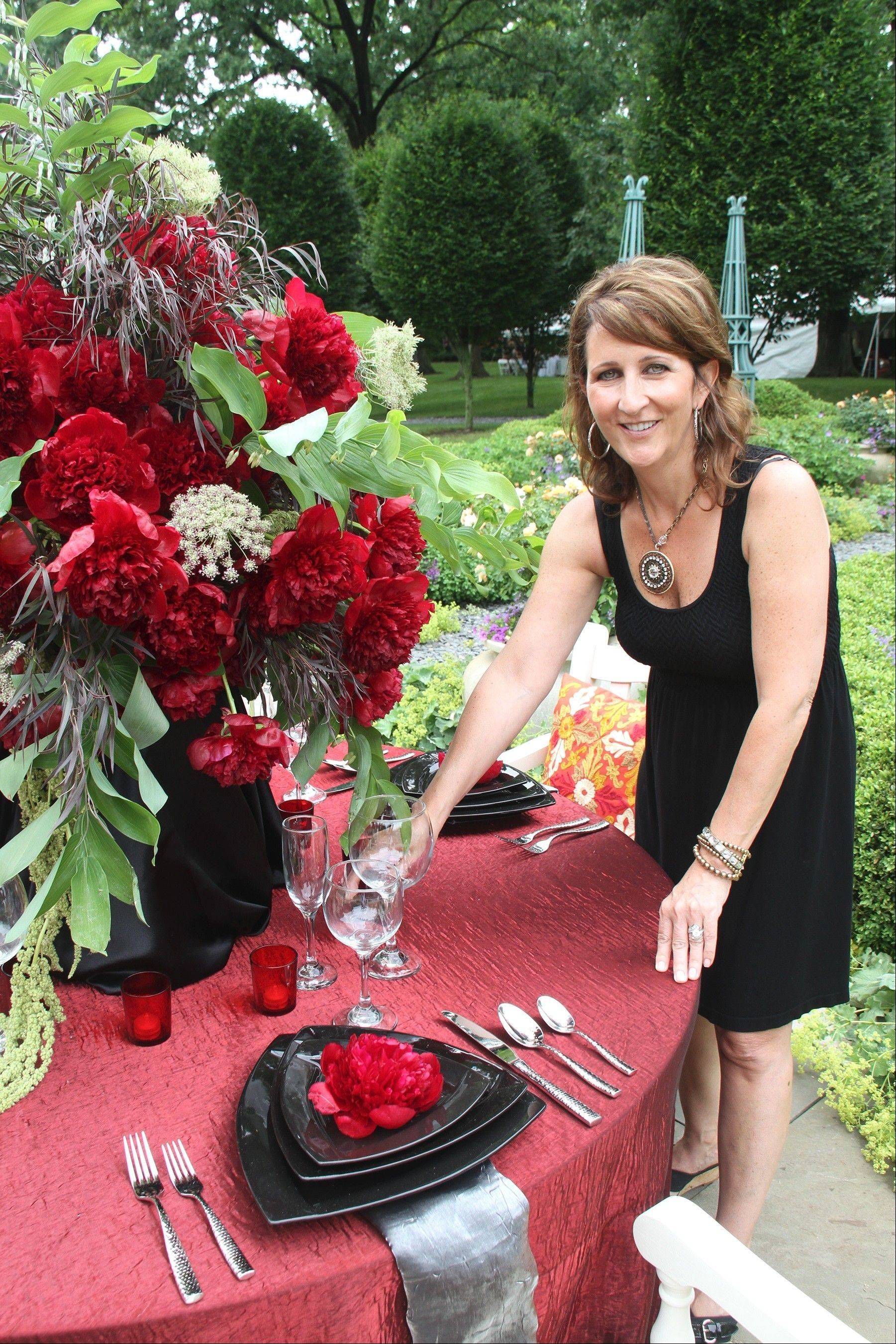 Sue Foley, co-owner of POSH Services, adds the finishing touches to a vignette at Garden #1 in preparation for the 13th annual Barrington Country Garden & Antique Faire. The event last month drew more than 850 visitors.