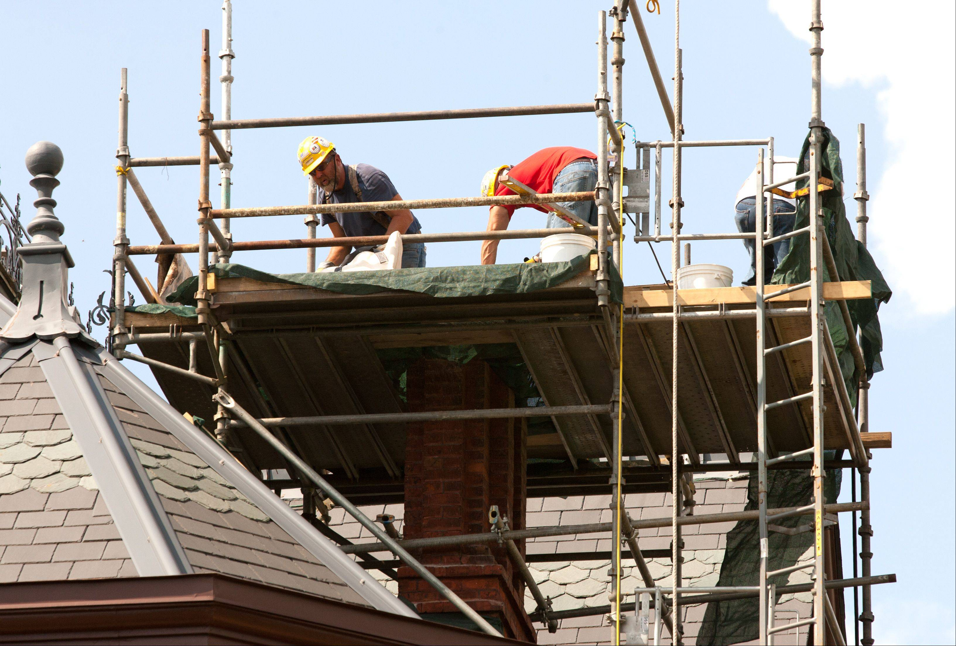 Workers from Berglund Construction of Chicago restore one of two tall chimneys at the Martin Mitchell Mansion on the grounds of Naper Settlement in Naperville. The city council on Tuesday night approved a $69,125 contract for emergency chimney work at the historic building.