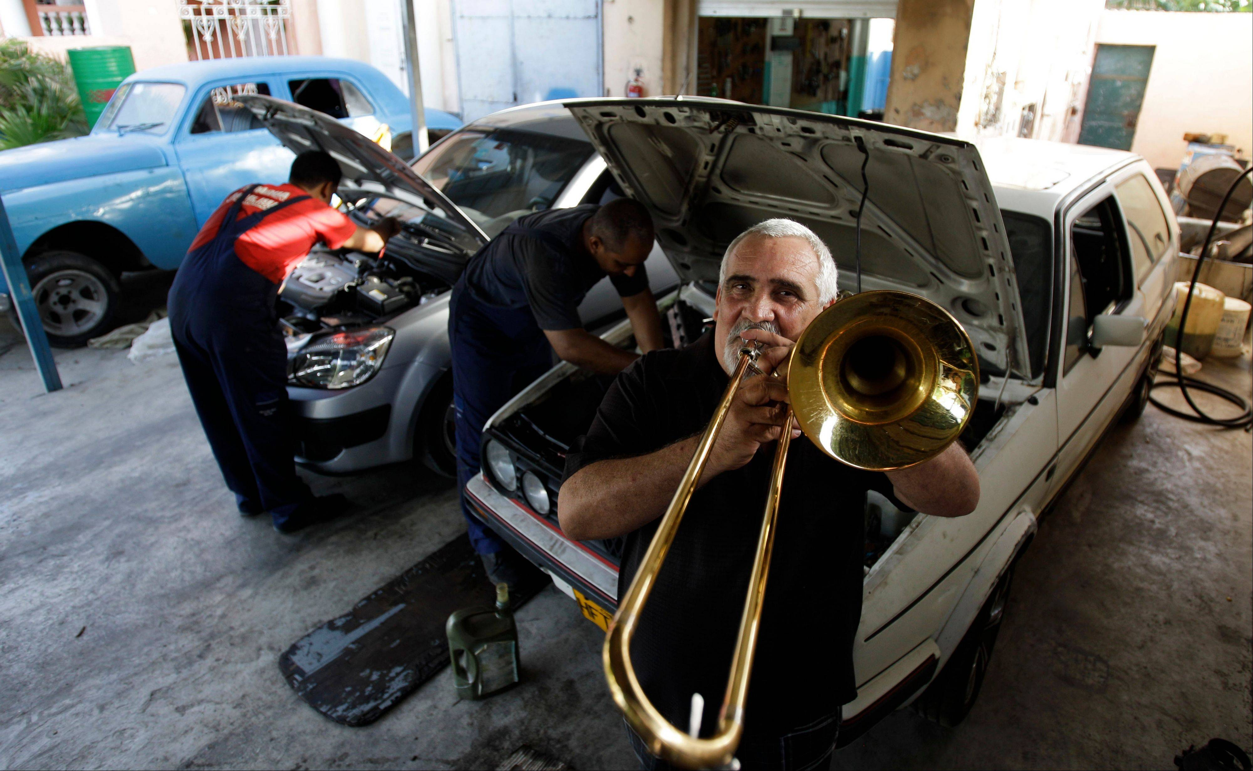 In this June 19, 2013 photo, Cuban Hugo Morejon, a trombonist in the contemporary salsa group, Los Van Van, poses for a photo in his automotive repair shop, Van Van Garage, in Havana. Armed with money and name recognition, Cuban athletes and artists who have long enjoyed a far more luxurious li