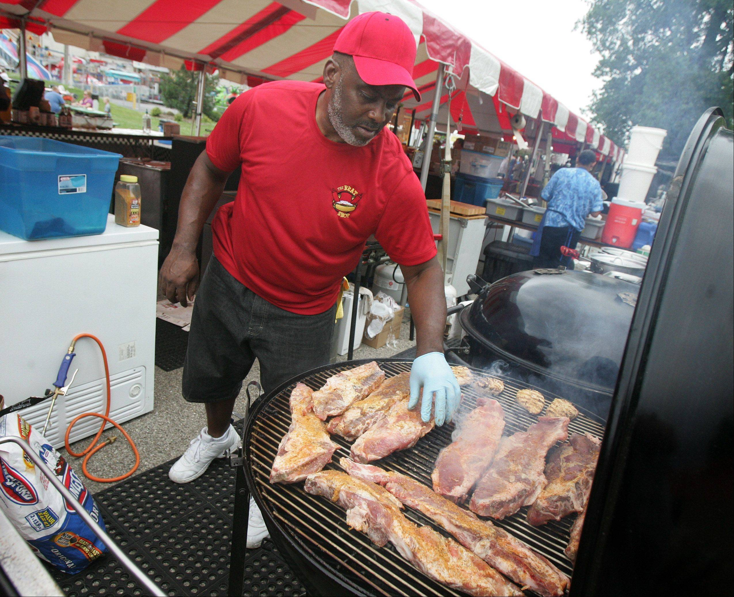 Chris Smith of the Brat Stop puts ribs on the grill during the first day of the Antioch Taste of Summer.