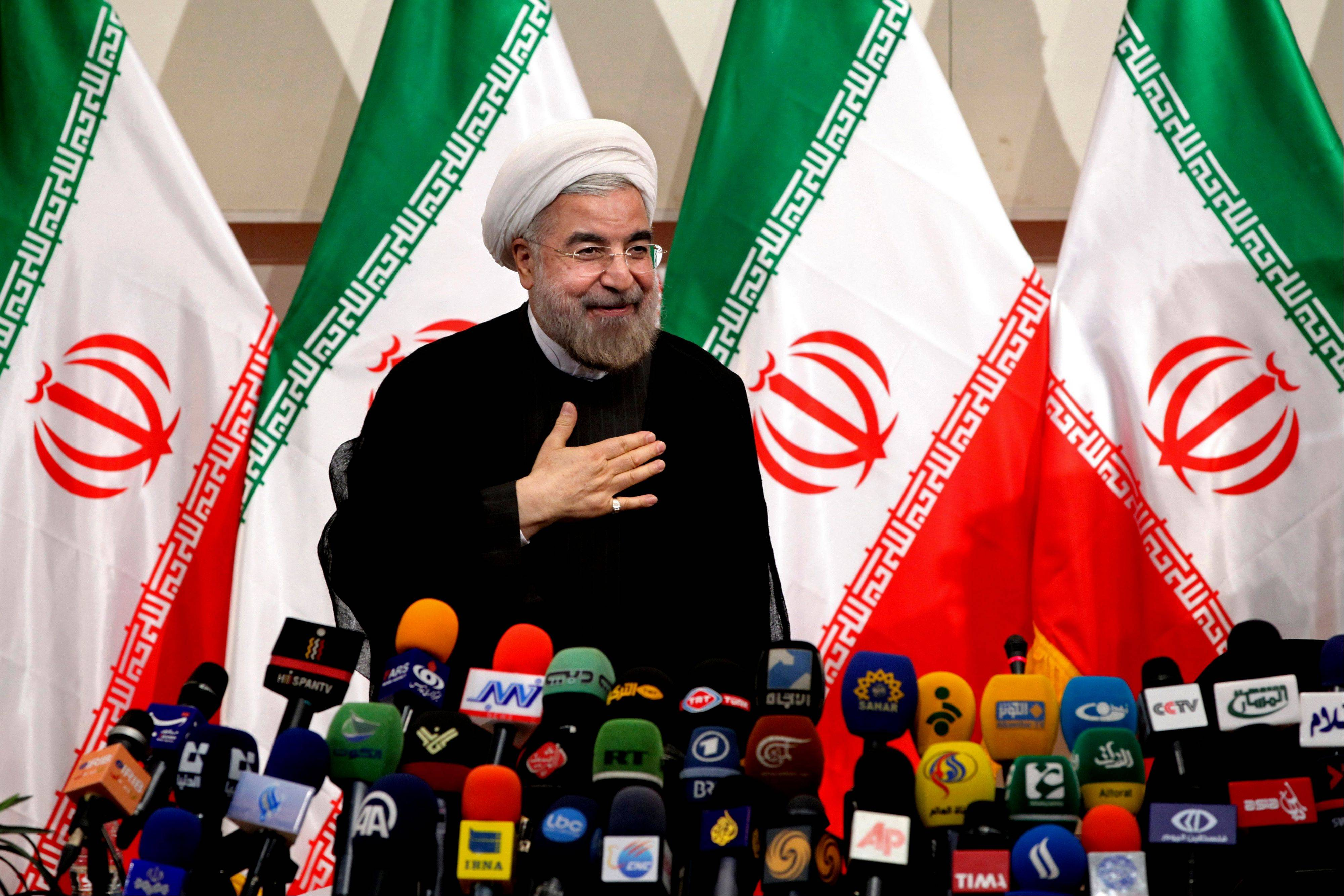Iranian President-elect Hasan Rouhani, places his hand on his heart as a sign of respect, after speaking at a news conference, in Tehran, Iran. Rouhani on Monday leveled his first criticism of the outgoing administration since June's election, saying it has mismanaged the country's economy.
