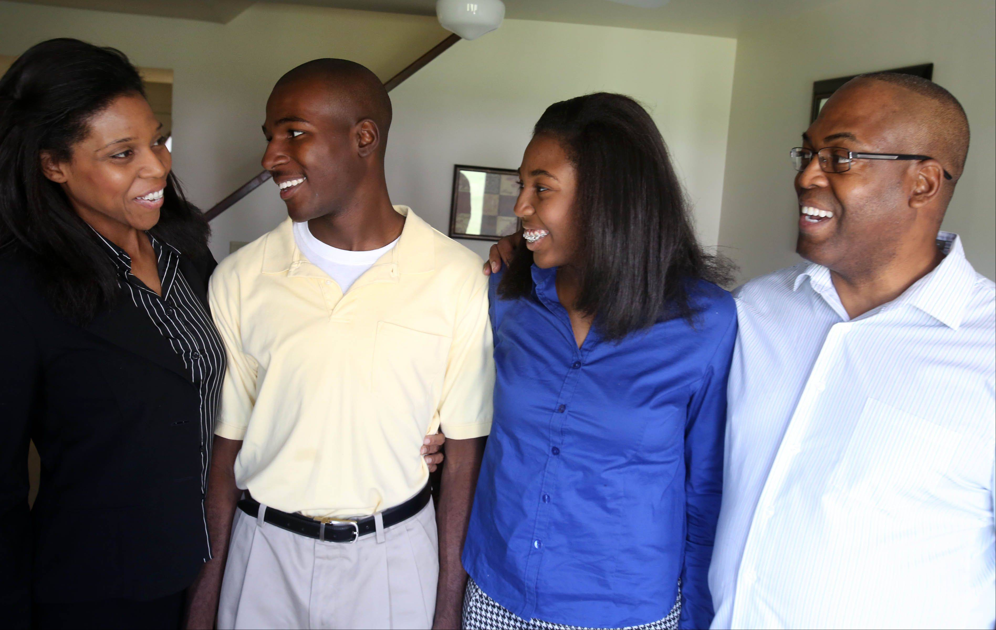 Thessalonika Arzu-Embry with her brother, Jeremy Embry, and her parents, Wonder and Carlos Embry, at their home at Great Lakes. Thessalonika, 14, will be graduating from Chicago State University in August with a bachelor's degree in psychology.