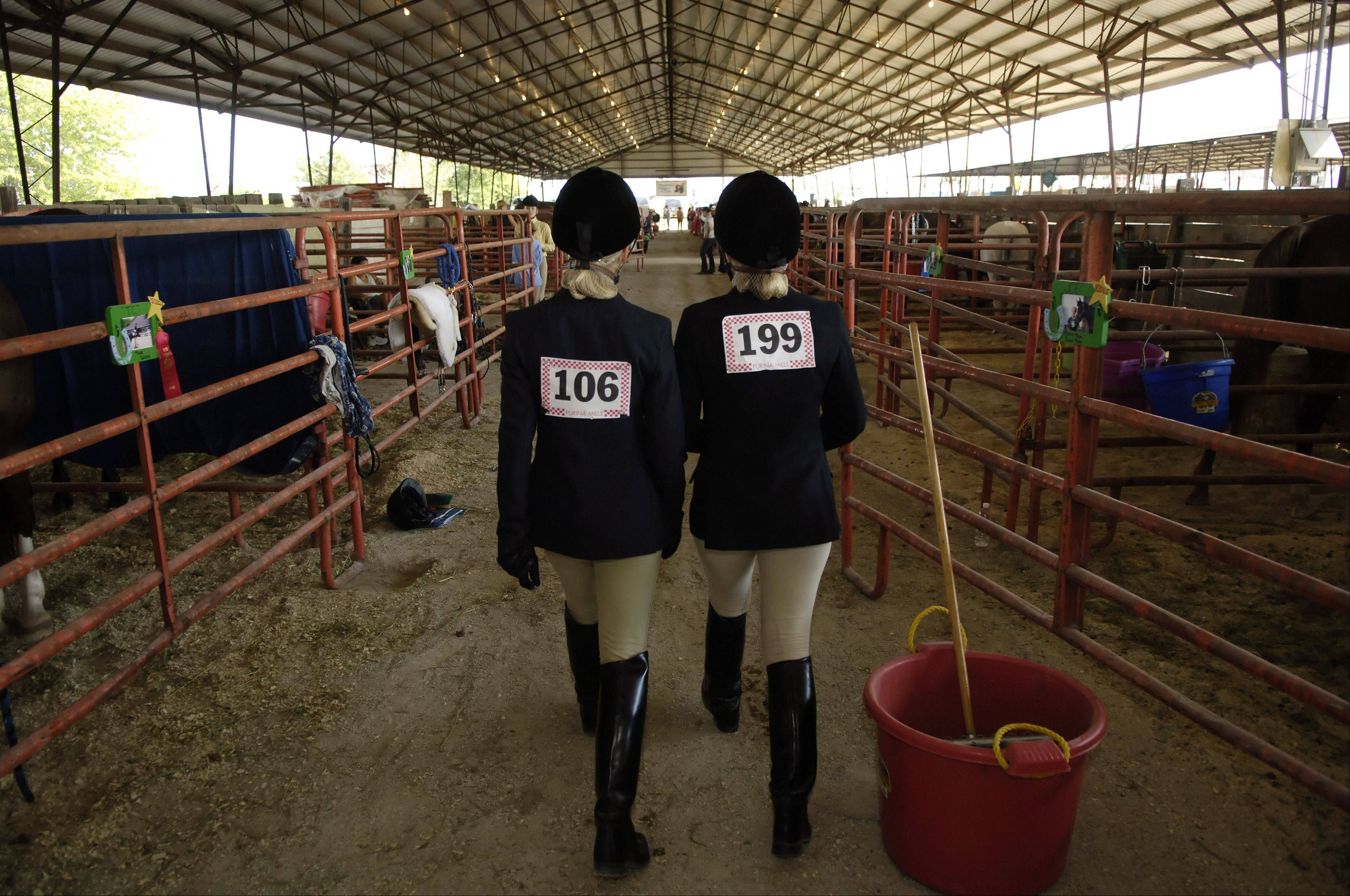 Dressed and ready to go, Alyssa Peterson, 13, left, and Allison Weir, 14, both of St. Charles, head toward the check-in booth in the horse barn at the Kane County Fair to see if their turn to compete is coming up.