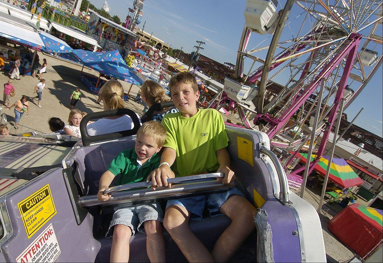 From left, brothers Kevin White, 4, and Brian White, 10 of Warrenville take a spin on the Wipeout ride at the Kane County Fair in St. Charles. The fair opens Wednesday, July 17, and runs through Sunday, July 21.