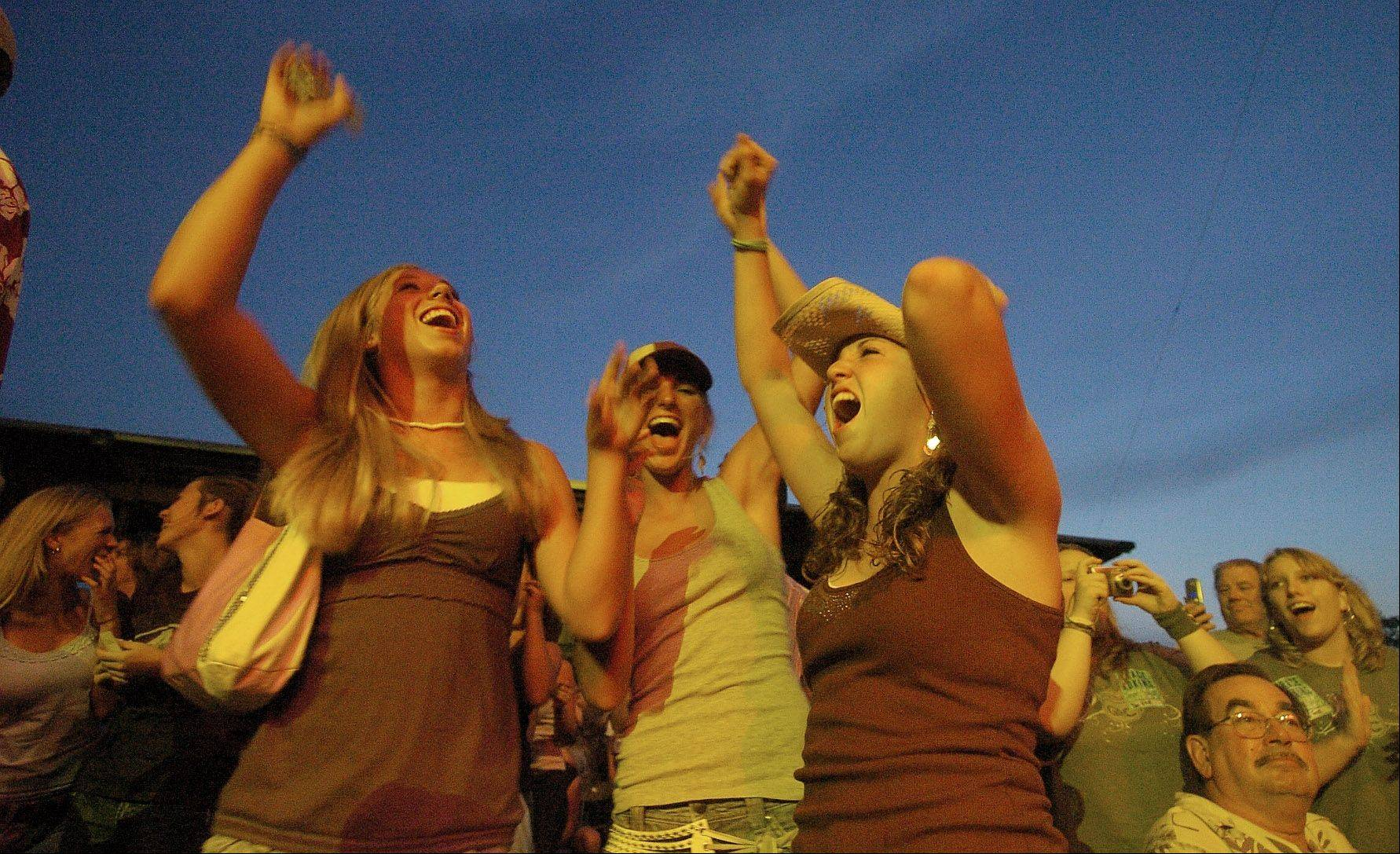 Friends Julie Buchra, Katie Dorsch and Molly Fremgen, all of St. Charles, whoop it up during a concert at the Kane County Fair in St. Charles.