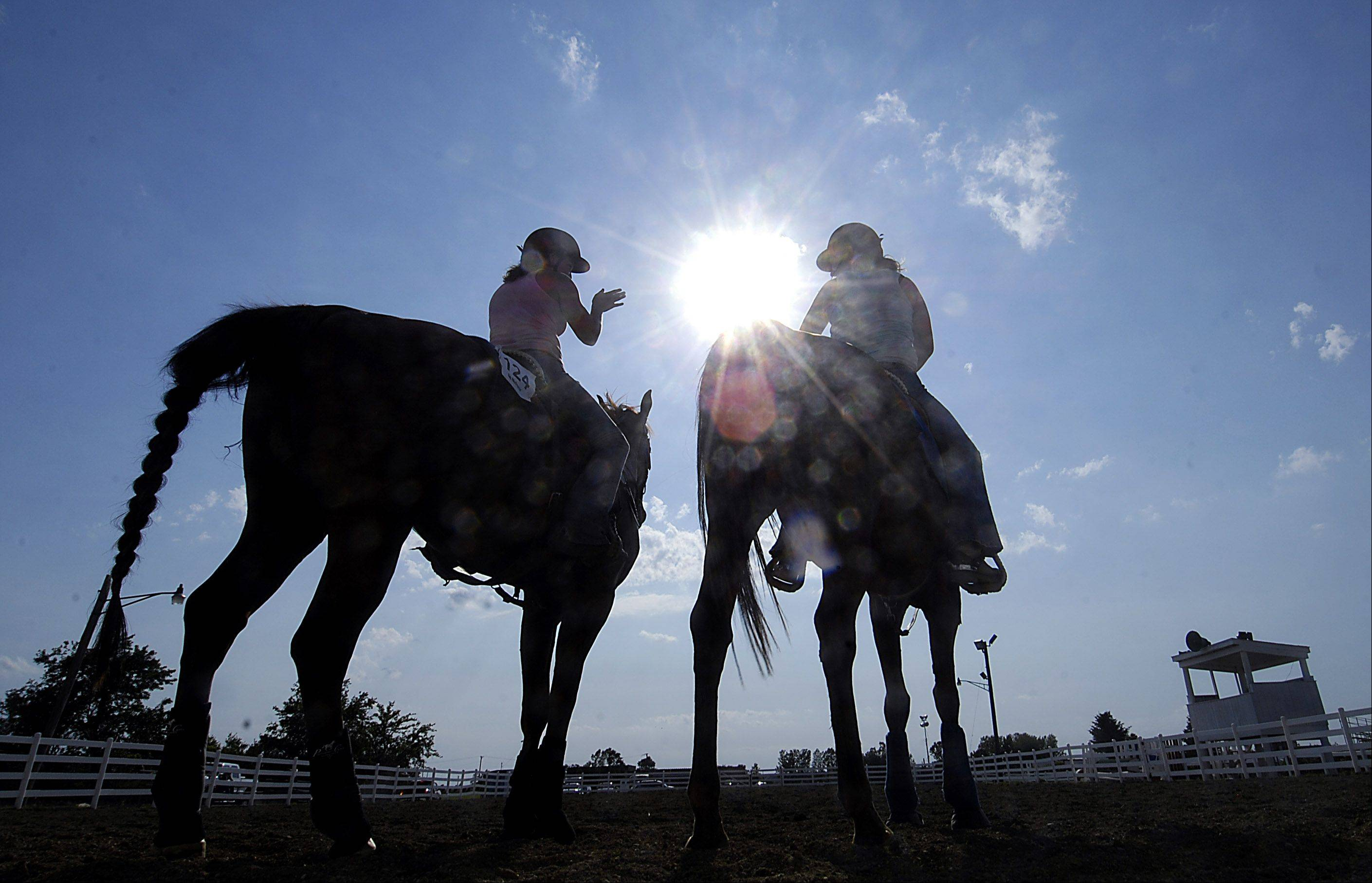 Nicole Stringer, 17, of Elgin, left, and Dakota Mision, 16, of Maple Park exercise their barrel racing horses at the Kane County Fair.