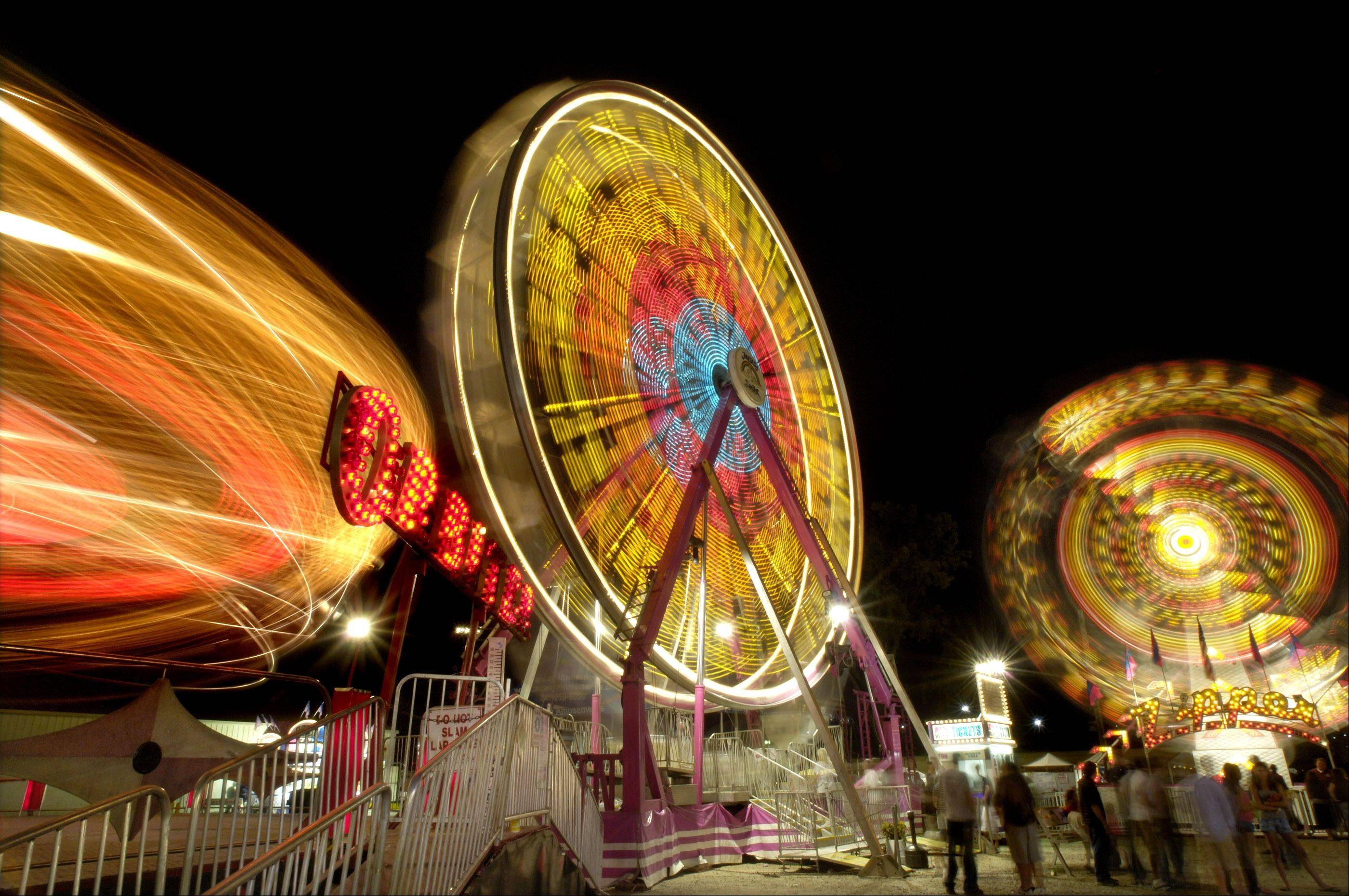 Like all midway rides, Orbiter, left, the Ferris wheel, and the Zipper, at right, spin in a regular pattern, and they light up like Christmas trees. The midway will be lit up with rides beginning Wednesday, July 17, when the Kane County Fair opens.
